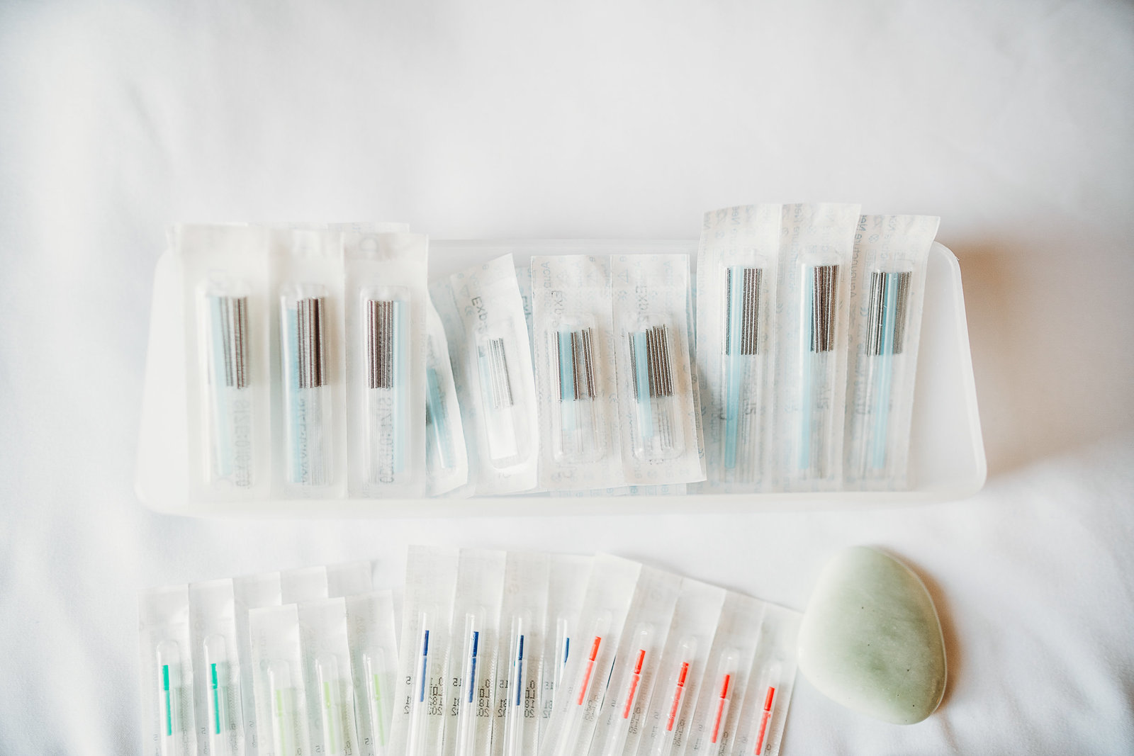 rainbow colored acupuncture needles laid out on a white sheet