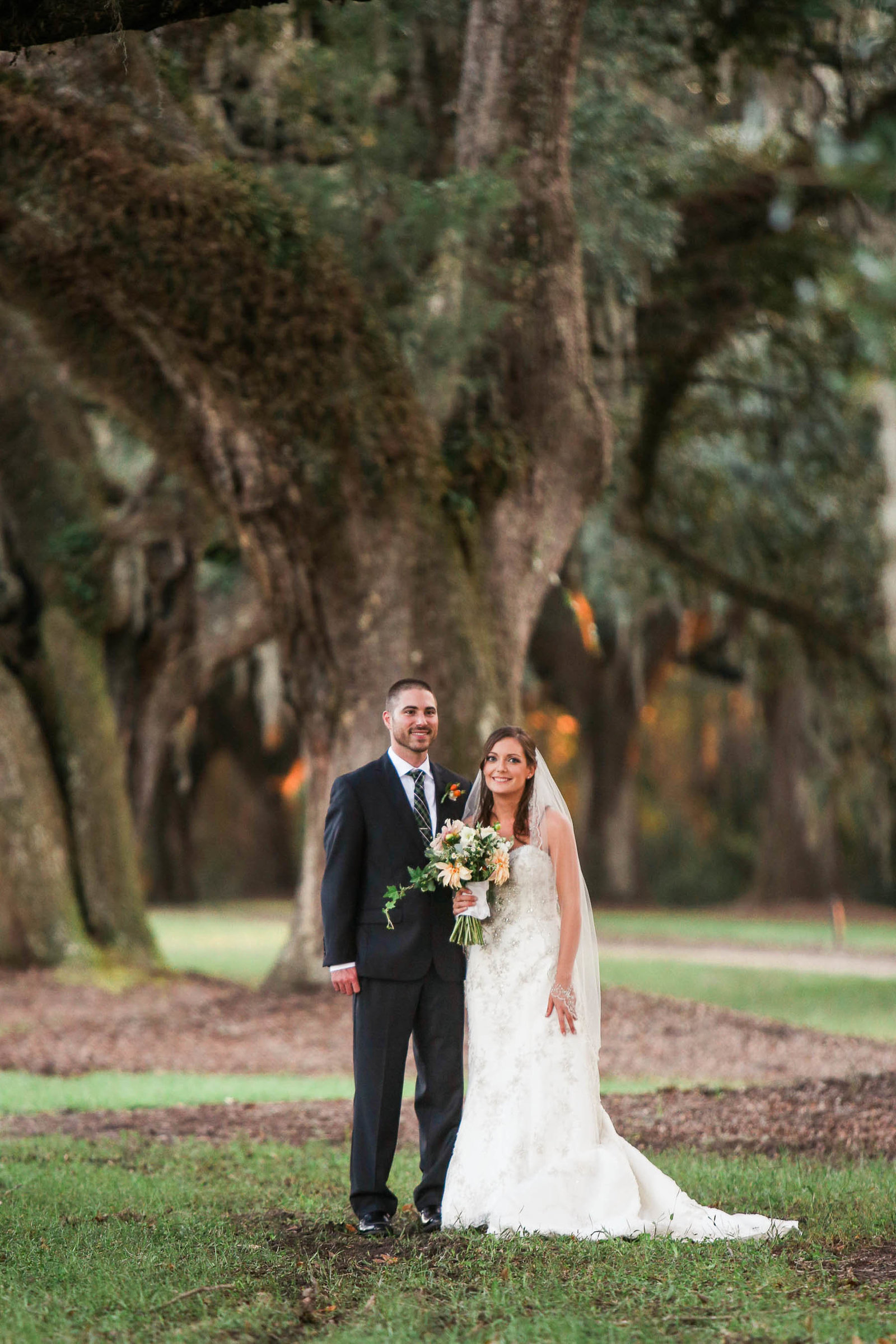 Bride and groom stand by oak tree, Boone Hall Plantation, Charleston, South Carolina