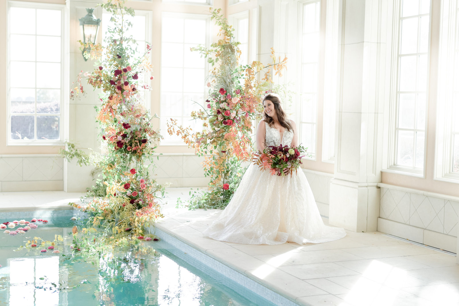 Gorgous bride stands with bouquet in front of floral installation next to pool