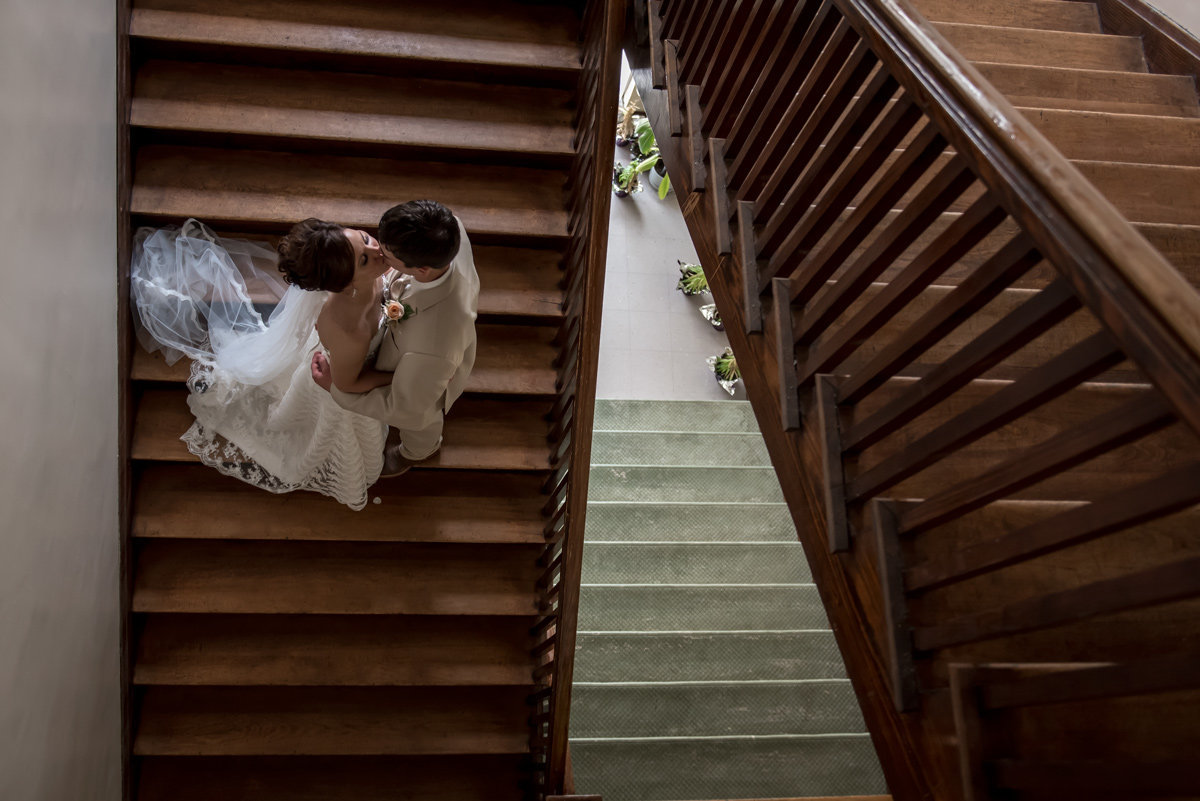 bride and groom kissing on stairs