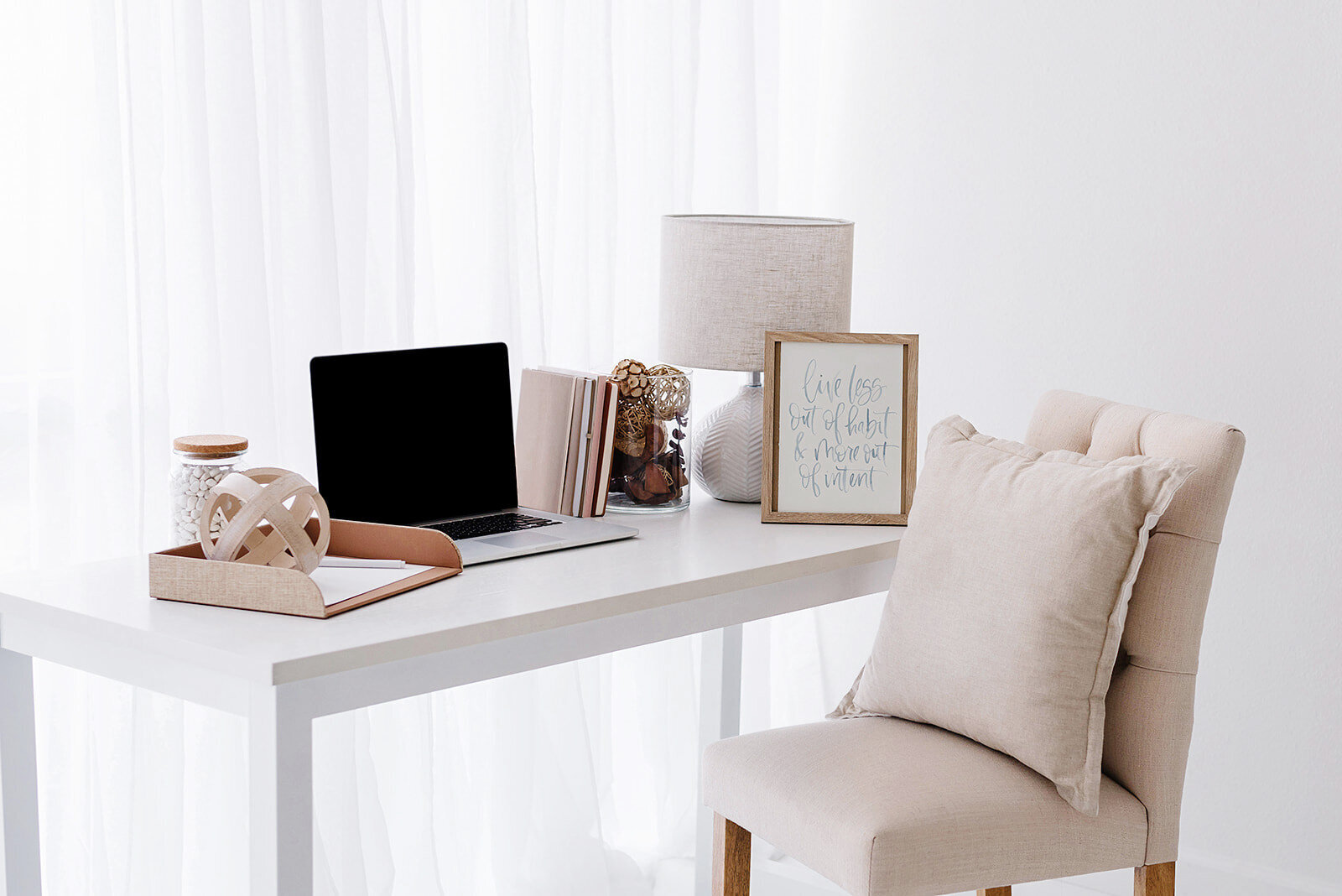 small business owner's home office, white table with pink chair and laptop