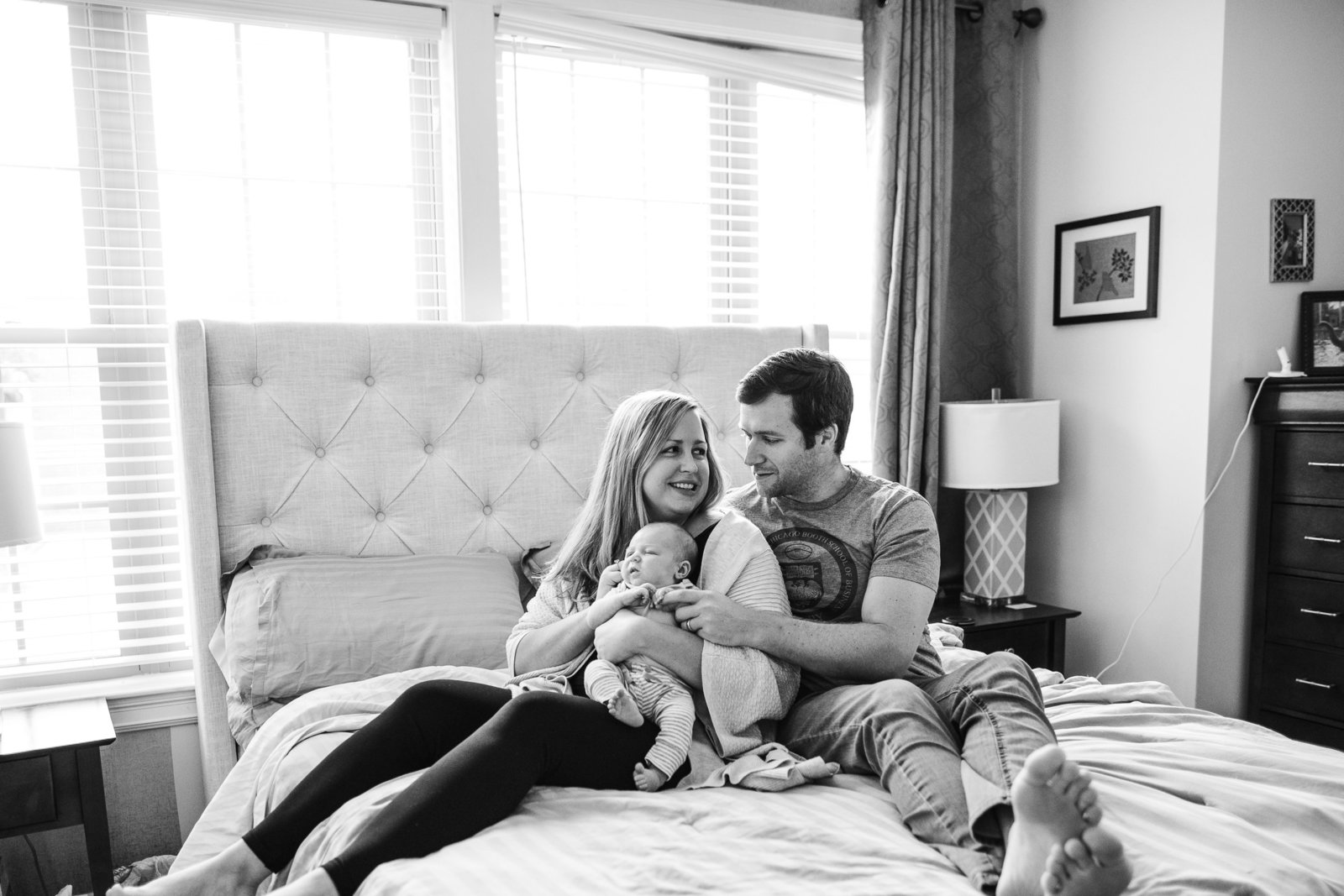 south boston couple hold baby boy sitting on master bed