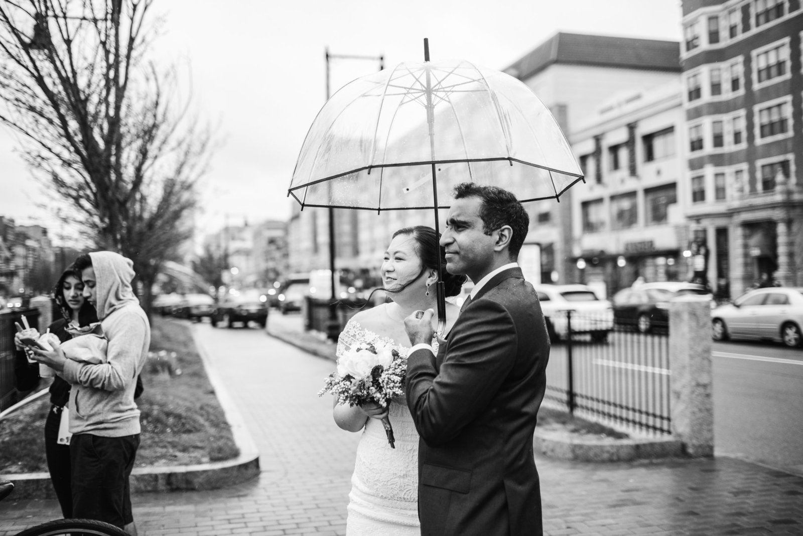 bride and groom share an umbrella on the streets of boston