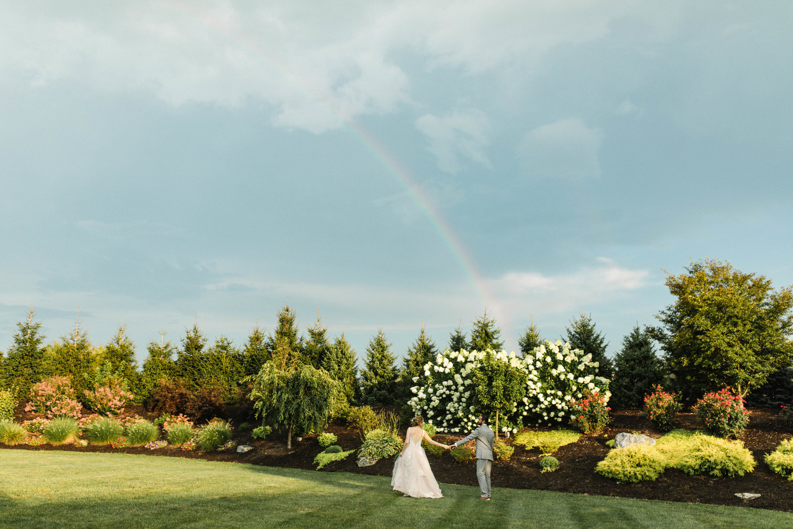 couple walking towards a rainbow at wedding