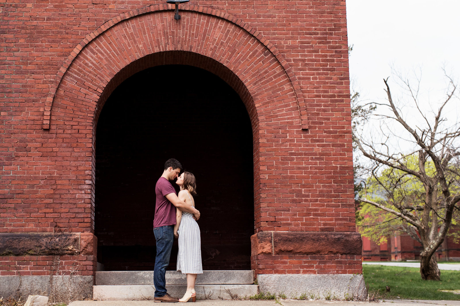 expectant couple stand under archway of brick building in medfield ma