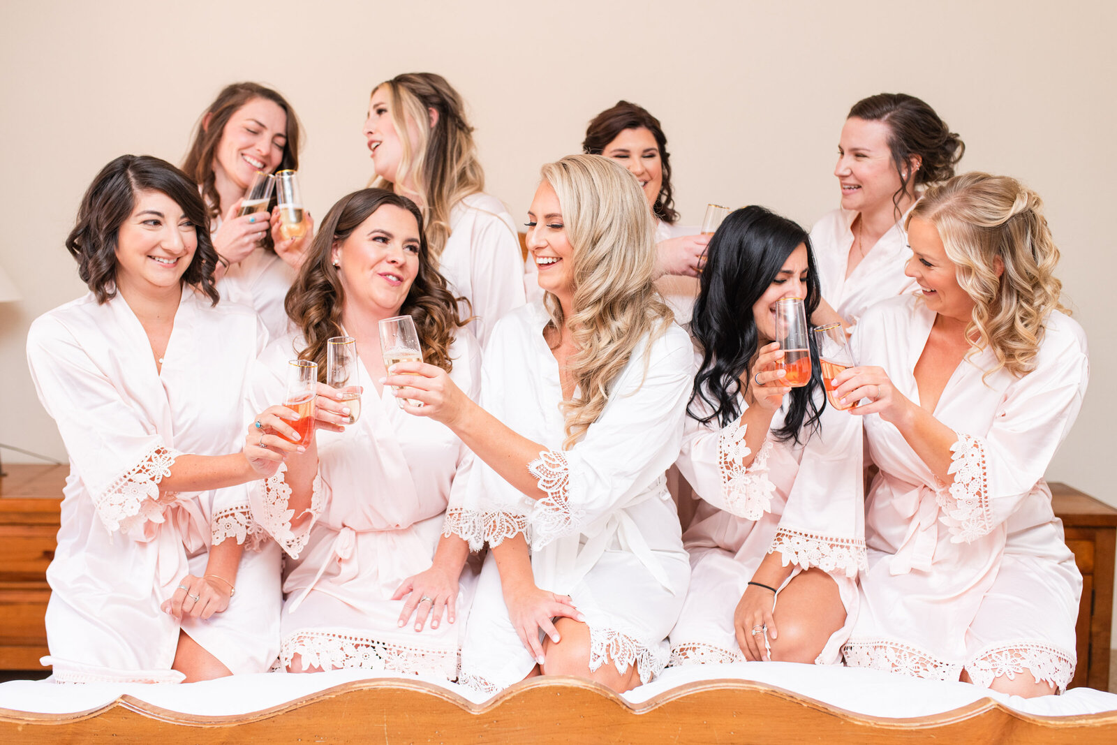 bride with bridesmaids in matching robes toasting with champagne