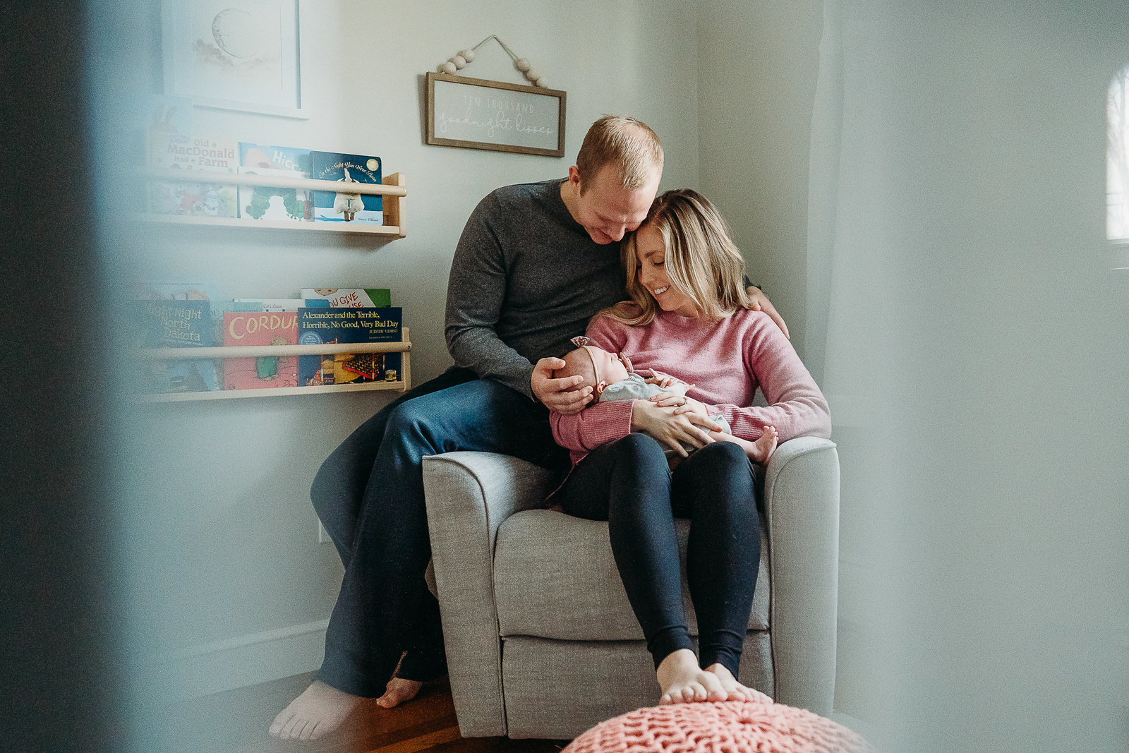 couple sits in armchair holding baby girl during newborn photoshoot in arlington ma