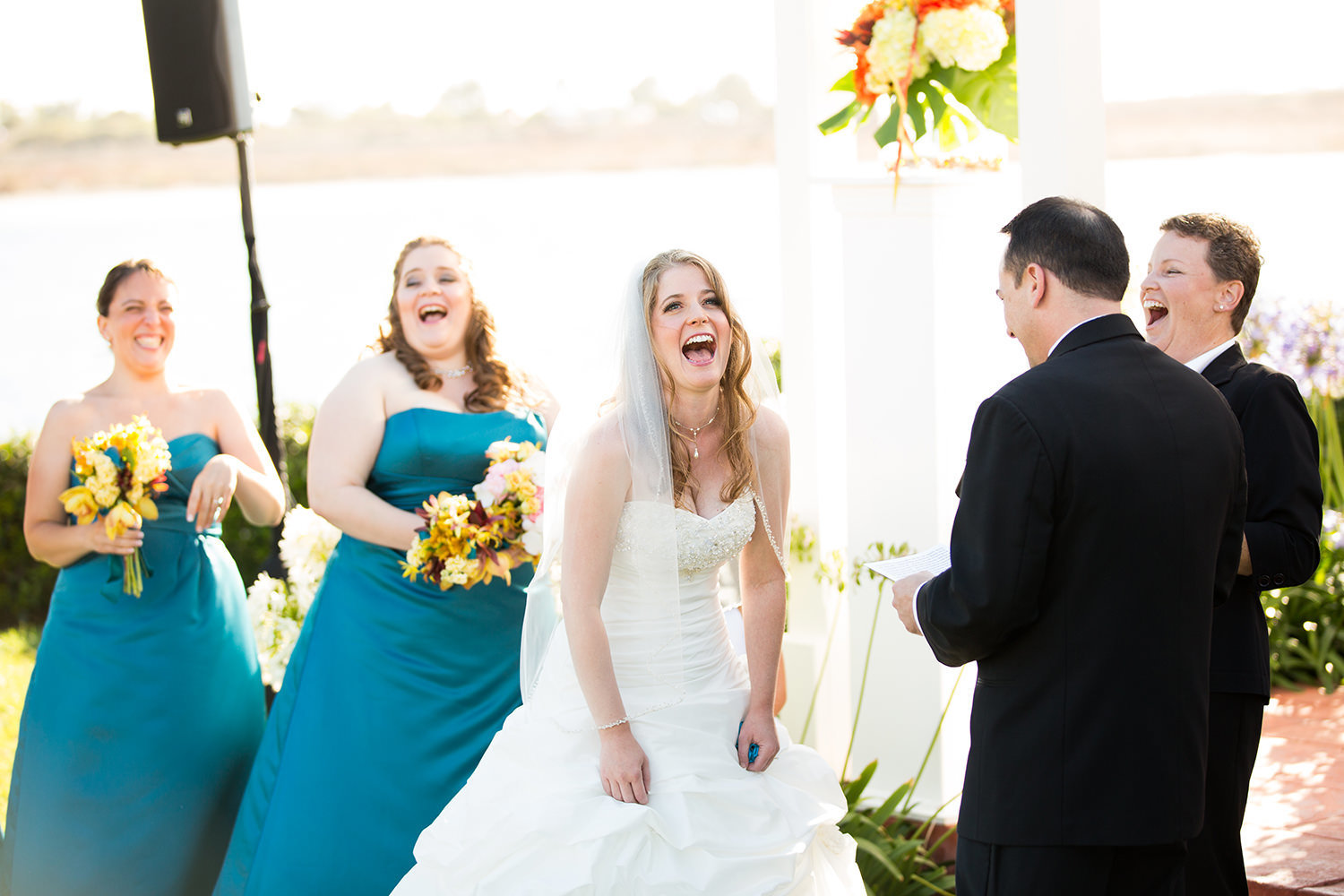 bride laughing at grooms speech at ceremony