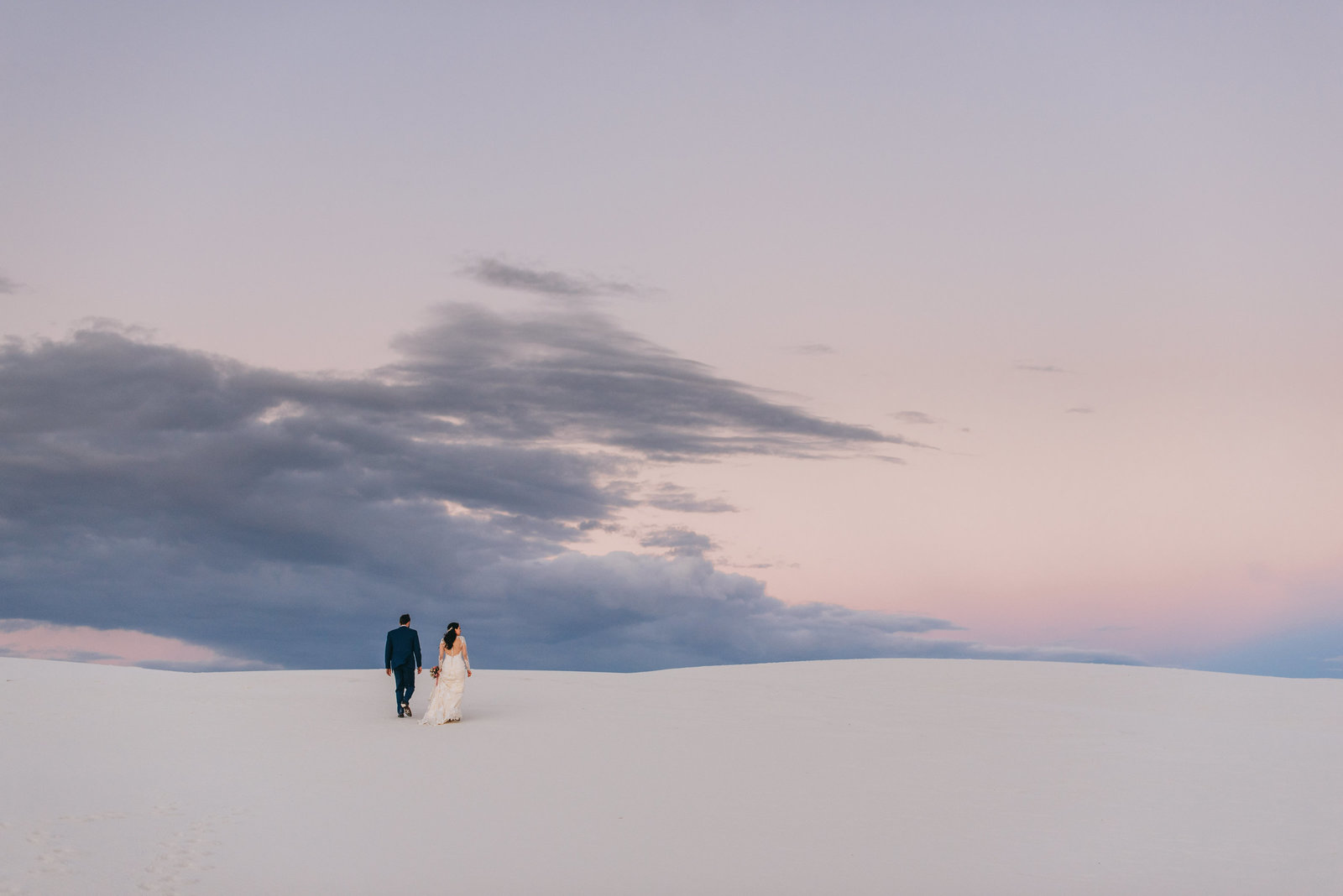 Couple walking through the  sand dunes of White Sands