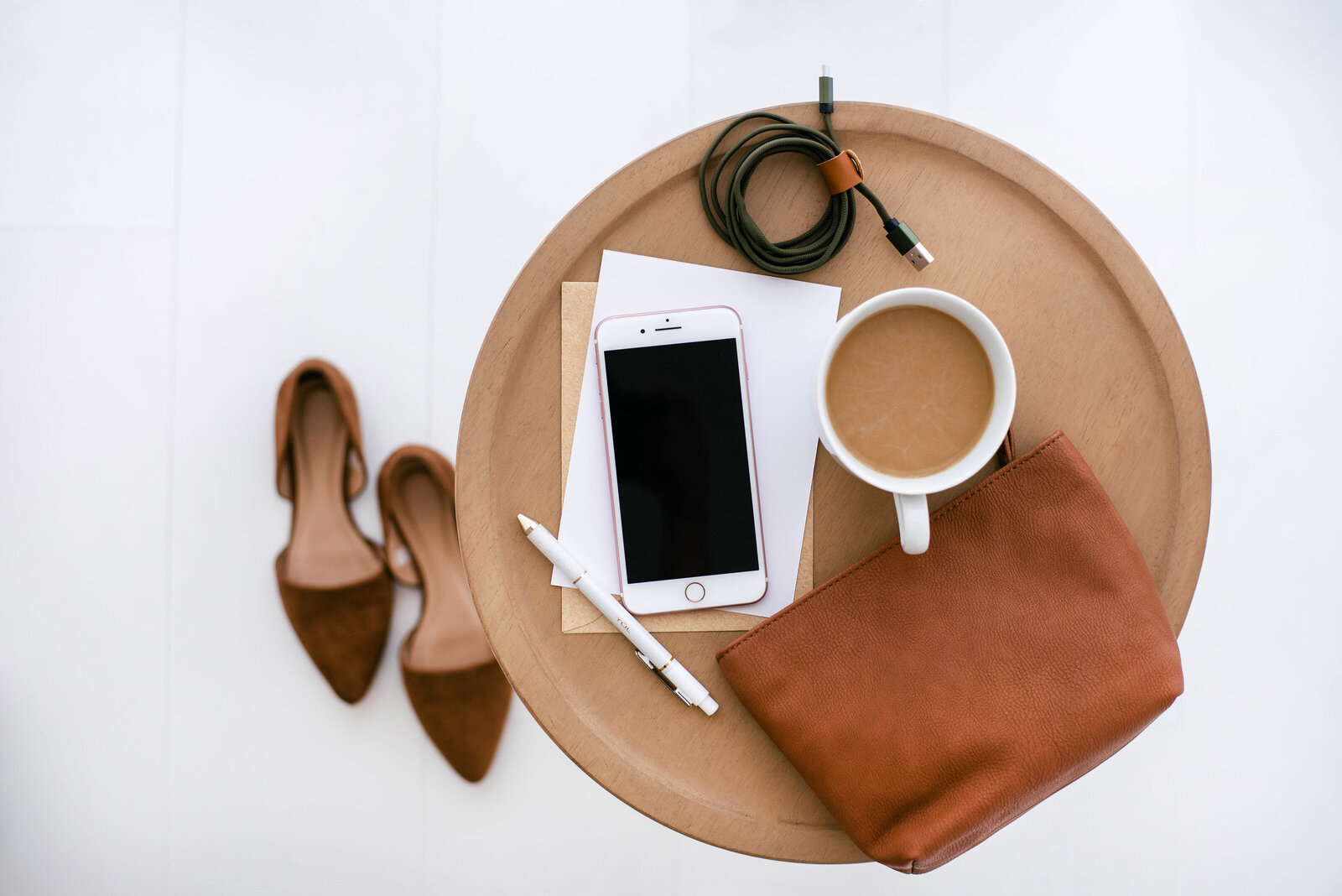 small business owner workspace with phone, keys, coffee, wallet and purse