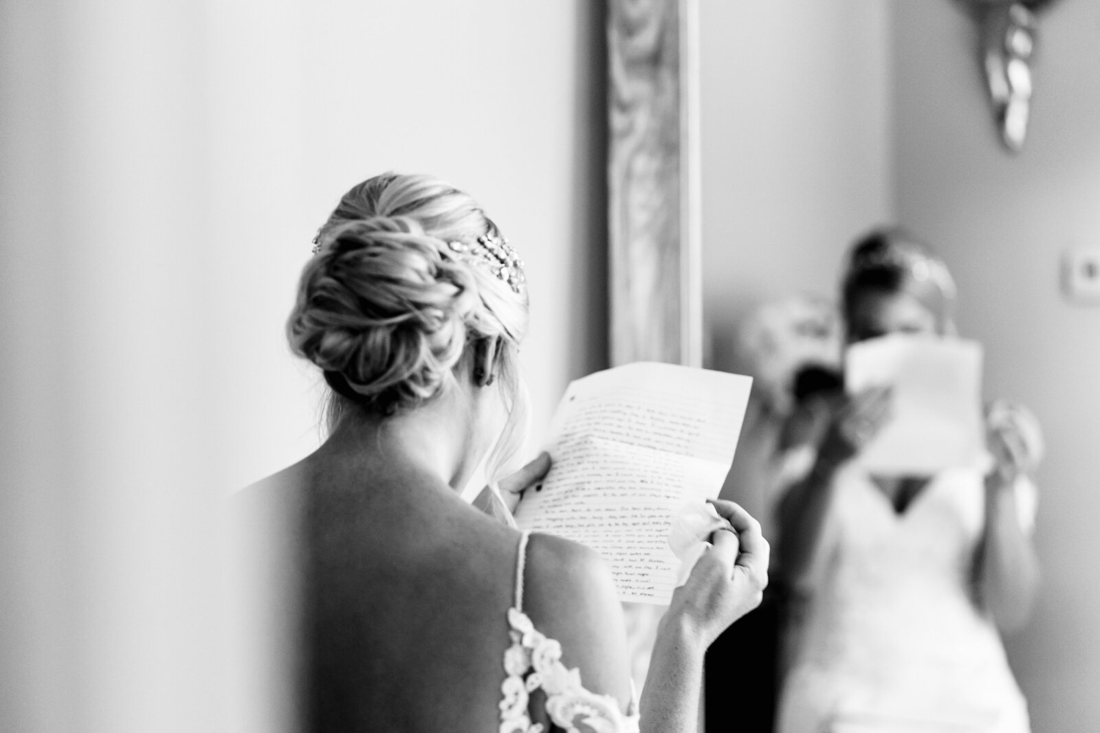 Black and white photo of bride reading note from groom before wedding