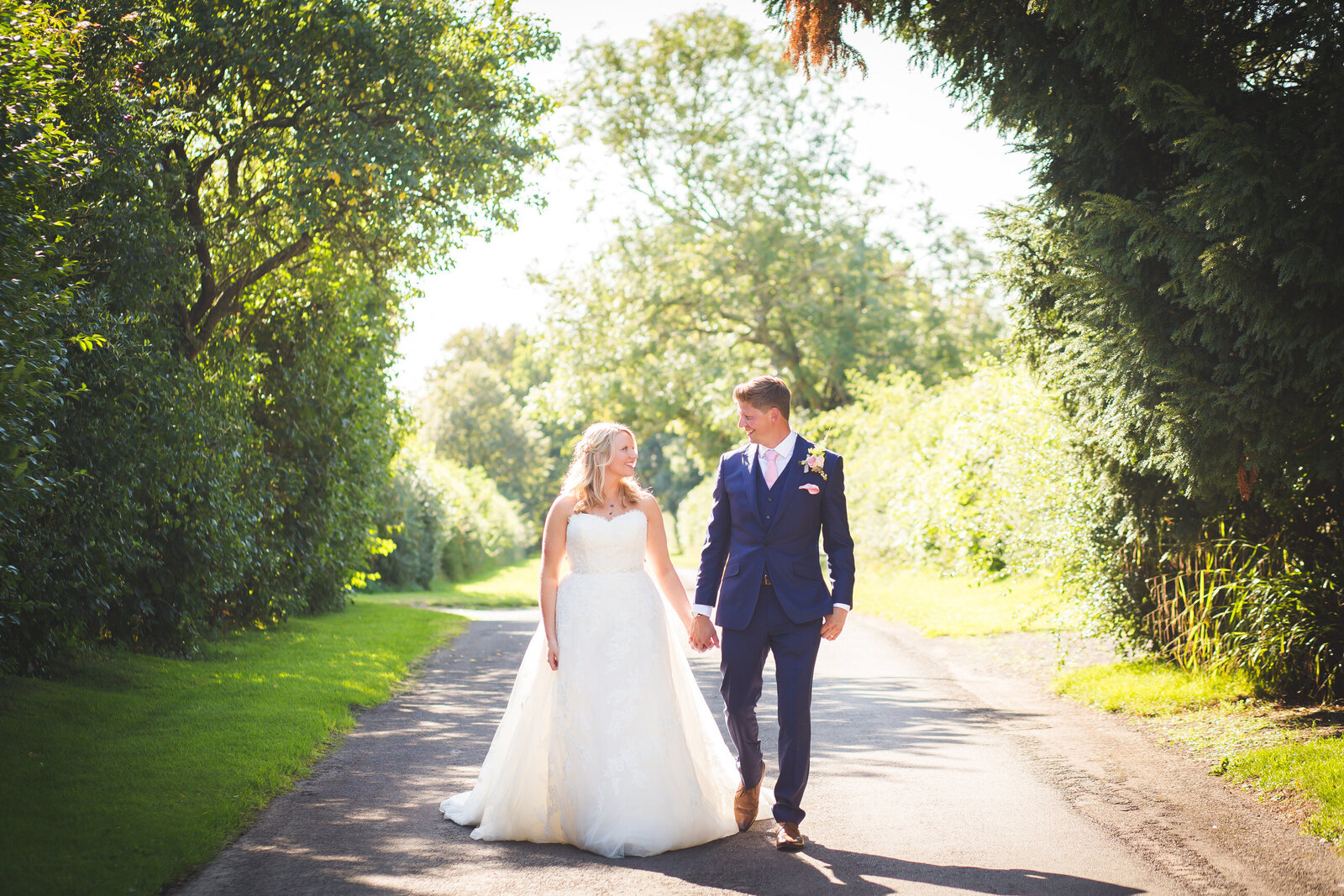 Wedding photography of bride and groom walking down road on their wedding day. Photography by Lynsey Grace Photography