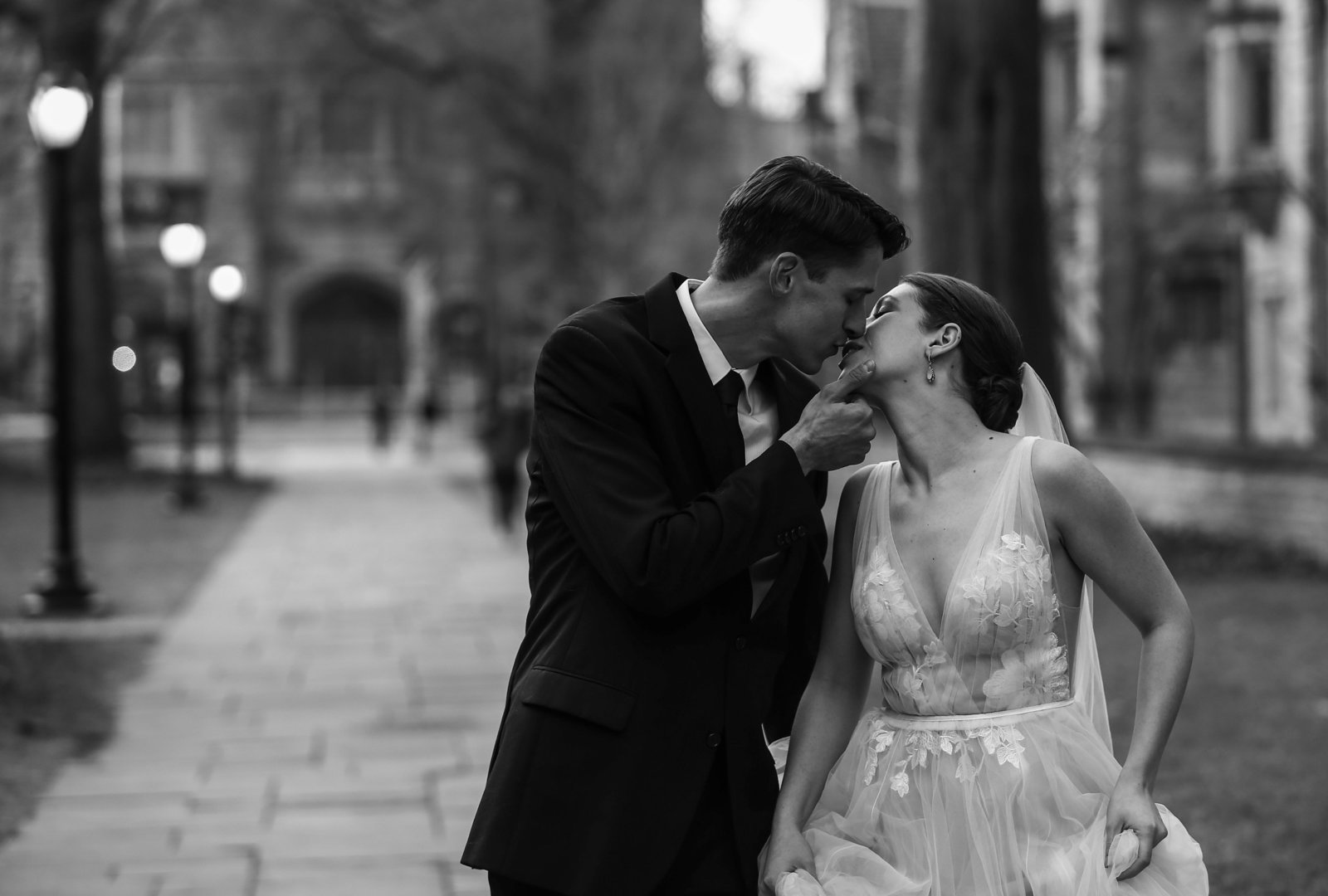 Bride and groom walk together and kiss on Yale University campus
