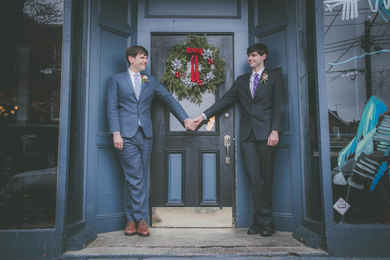 Gay couple hold hands against blue building during their elopement.