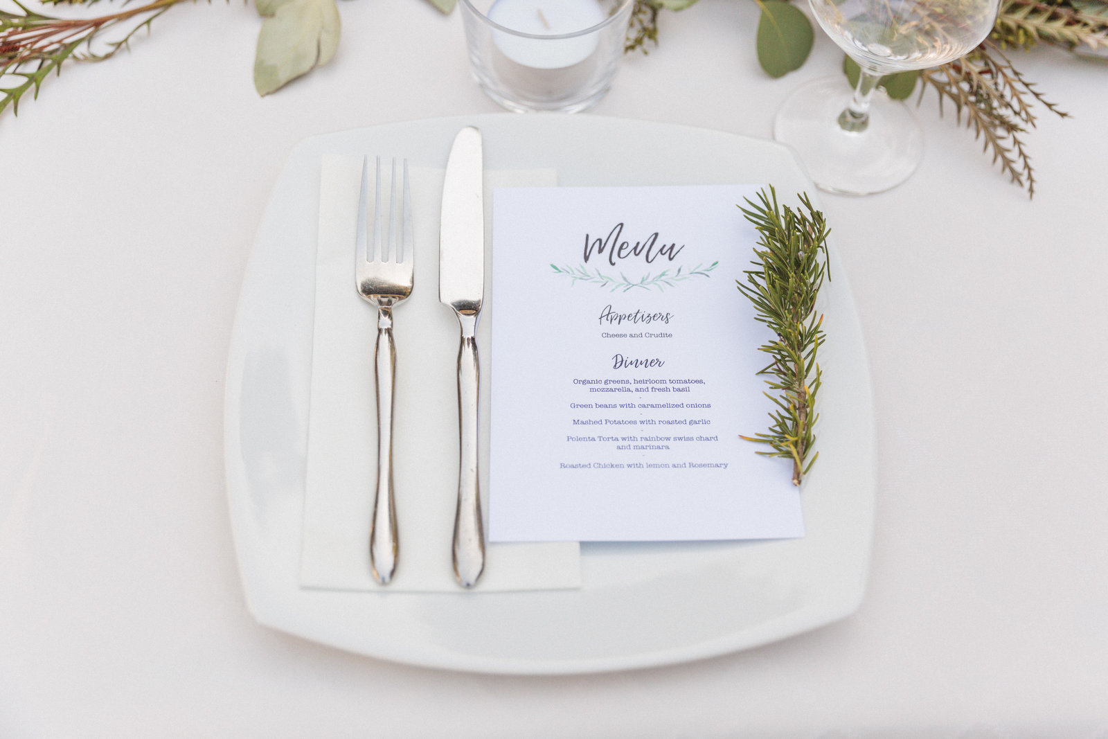 simple place setting with rosemary and white table linens at santa cruz wedding