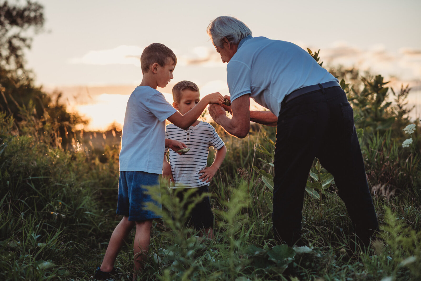 Grandfather and his grandsons in a field at sunset in Oshawa