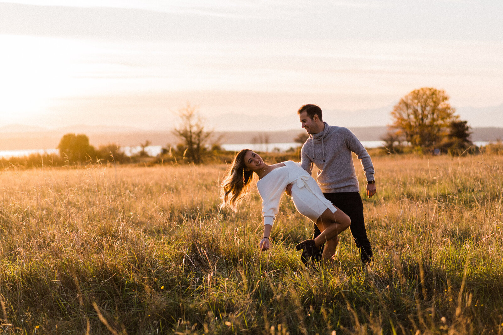 Couple dancing and hugging in large meadow at sunset in Discovery Park, best spot for engagement photos in Seattle