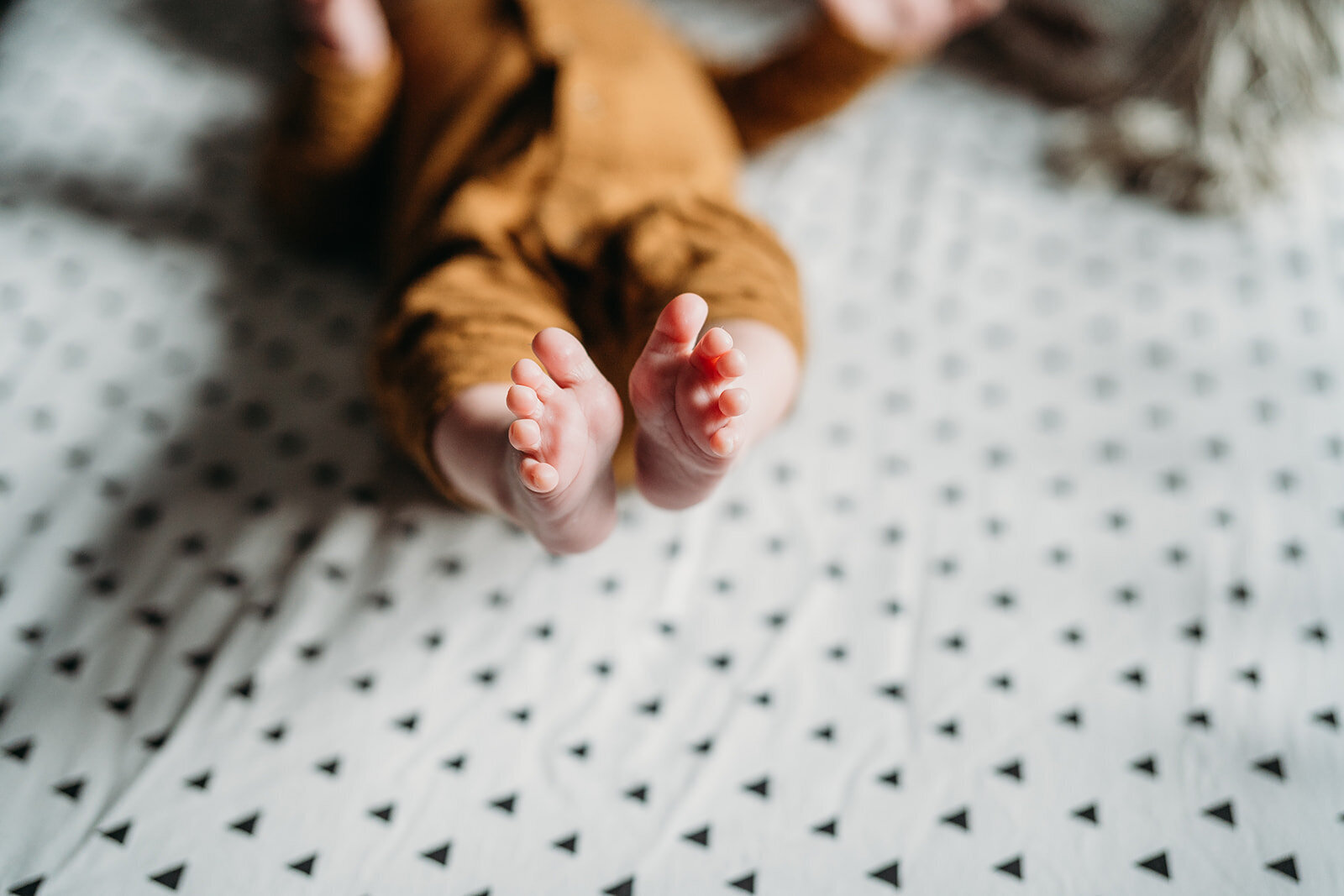 close up picture of baby toes on polka dot crib sheet