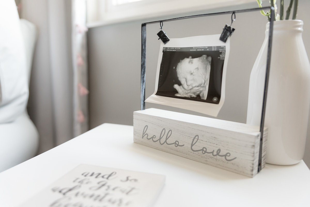 nursery decor includes ultrasound picture of new baby