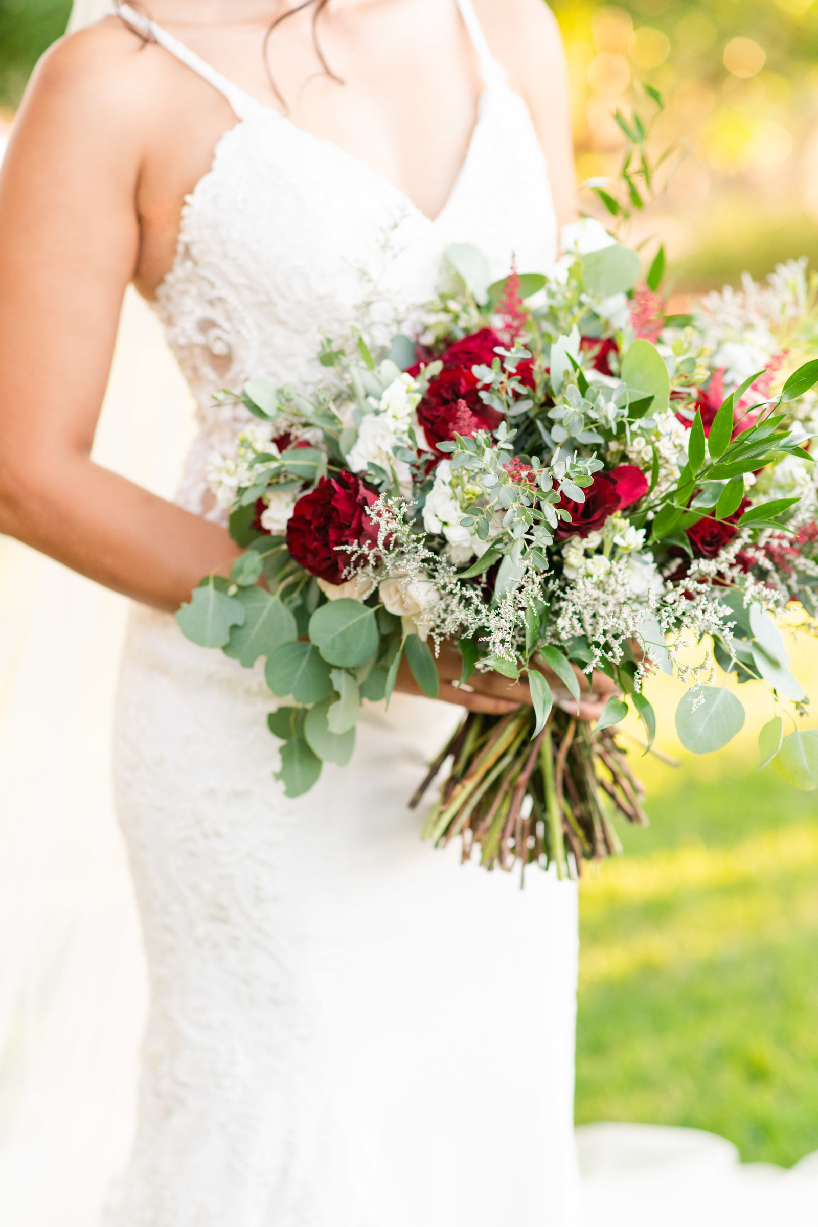 bride with bouquet of red roses on lawn at Reflections at the Buttes