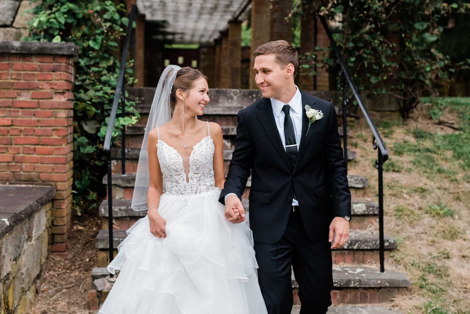 A couple walks the property at their Mansion at Turner Hill wedding