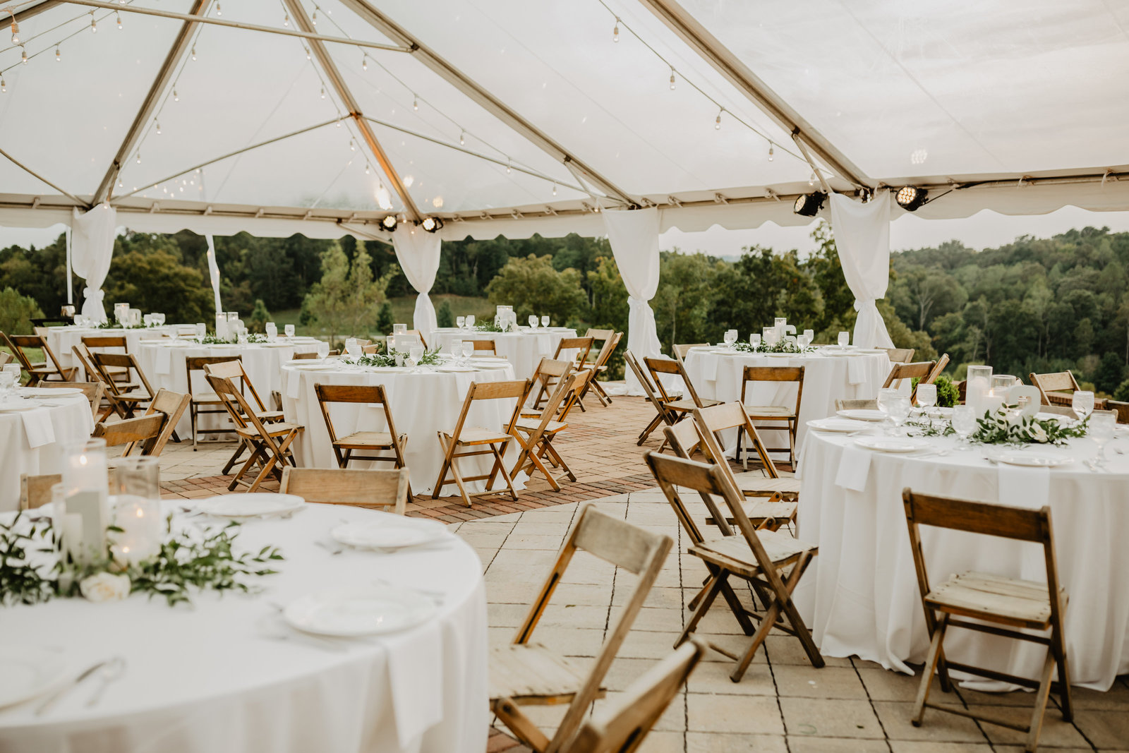 White tented reception table setup in simple green accents.