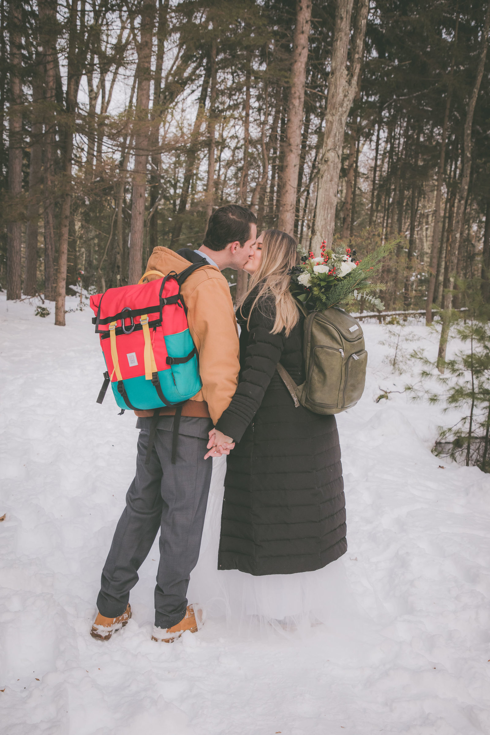 A couple kisses on a snow covered ground during their hiking elopement.