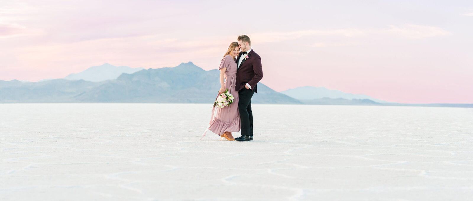 Couple in blush dress and burgundy suit at sunset at the Bonneville Salt Flats
