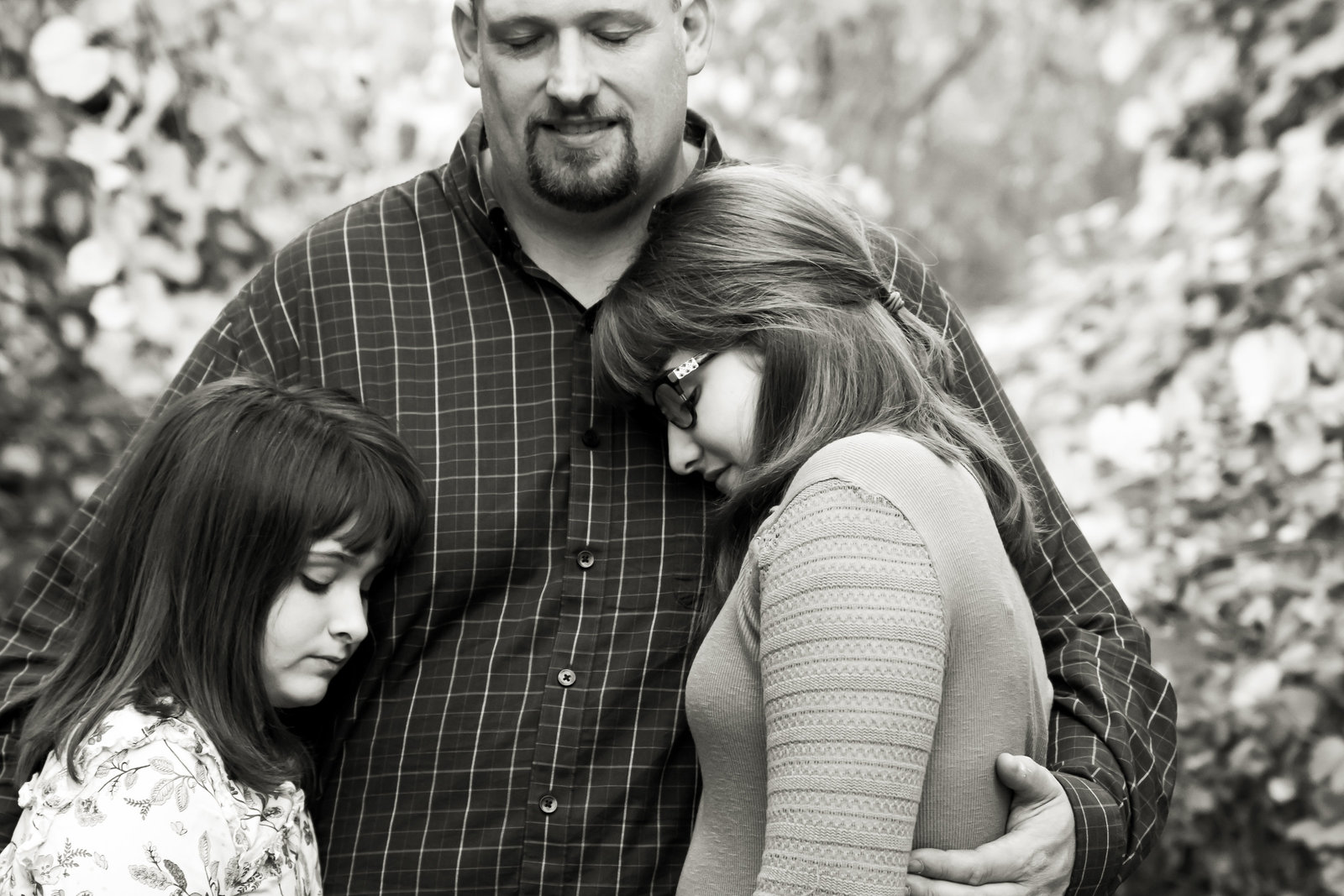 father hugging his two daughters