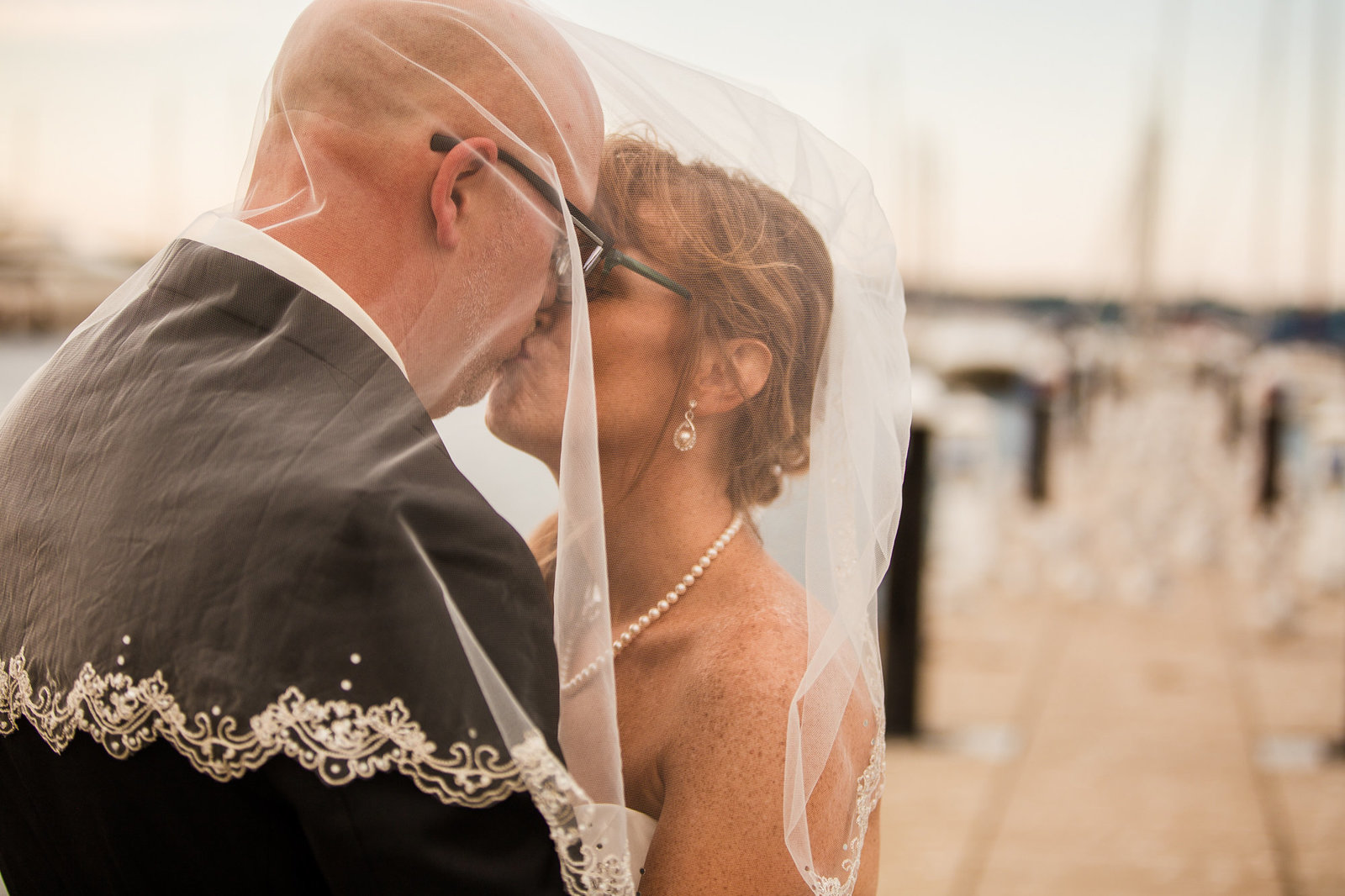 Bride and groom kiss under bride's veil on the dock at the Erie Yacht Club