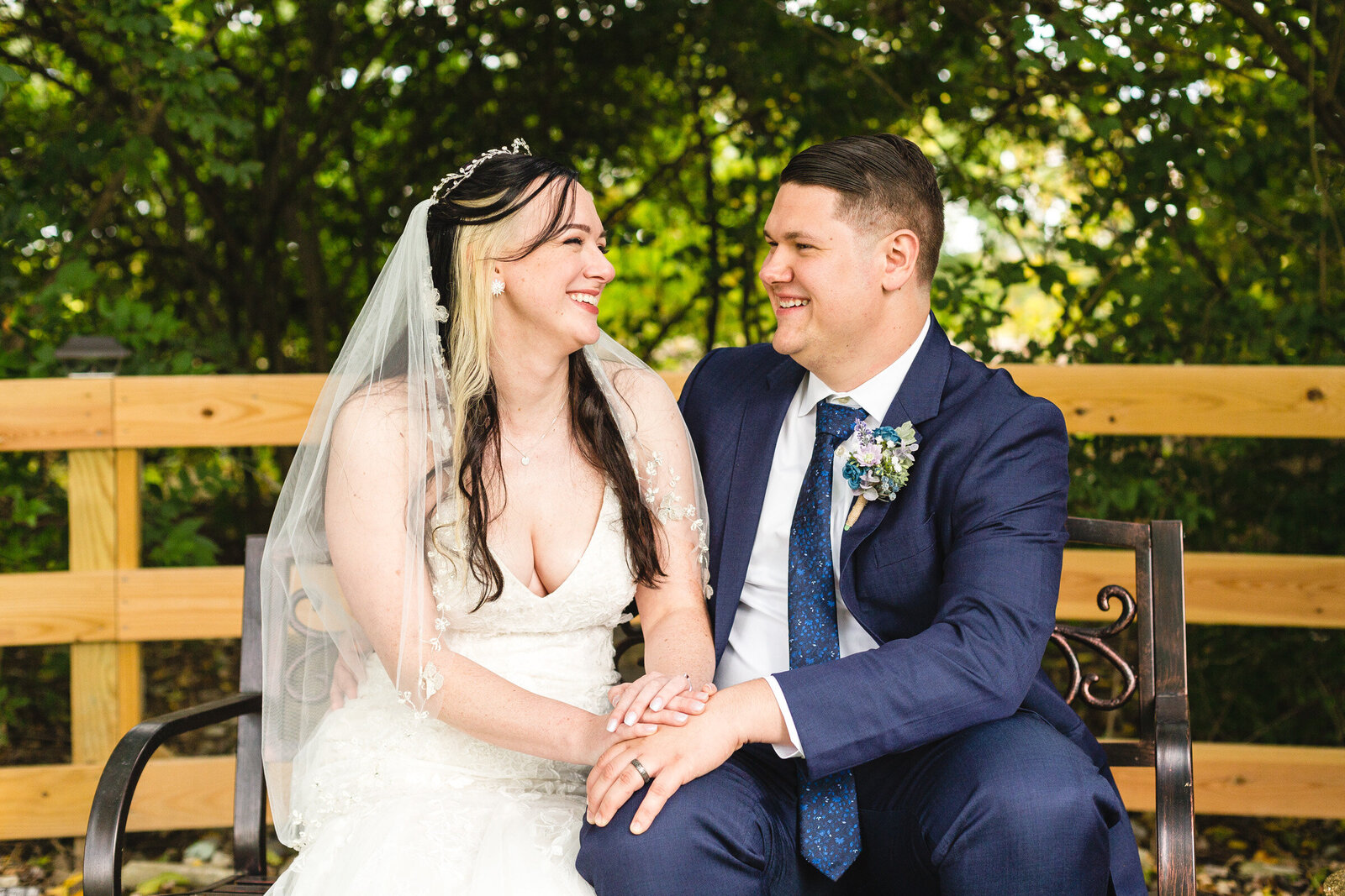 bride and groom laughing while sitting on a bench micro ohio wedding