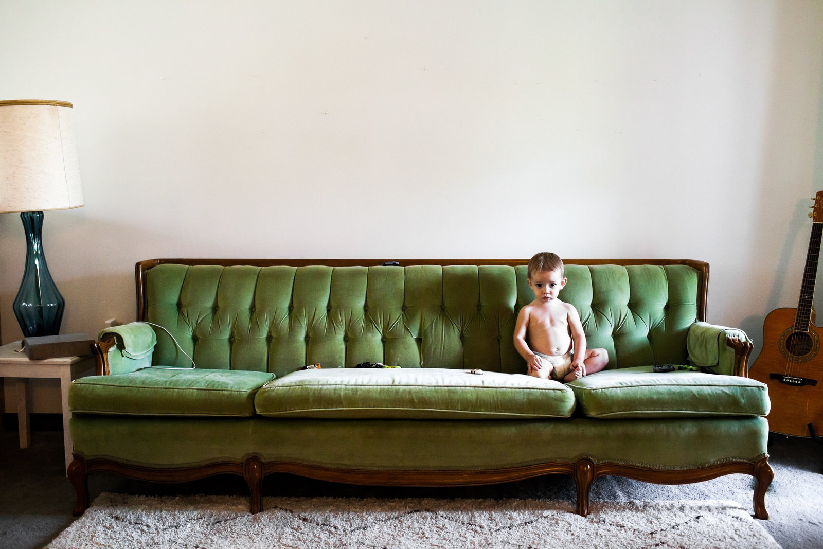 One year old in trendy home and green couch and guitar