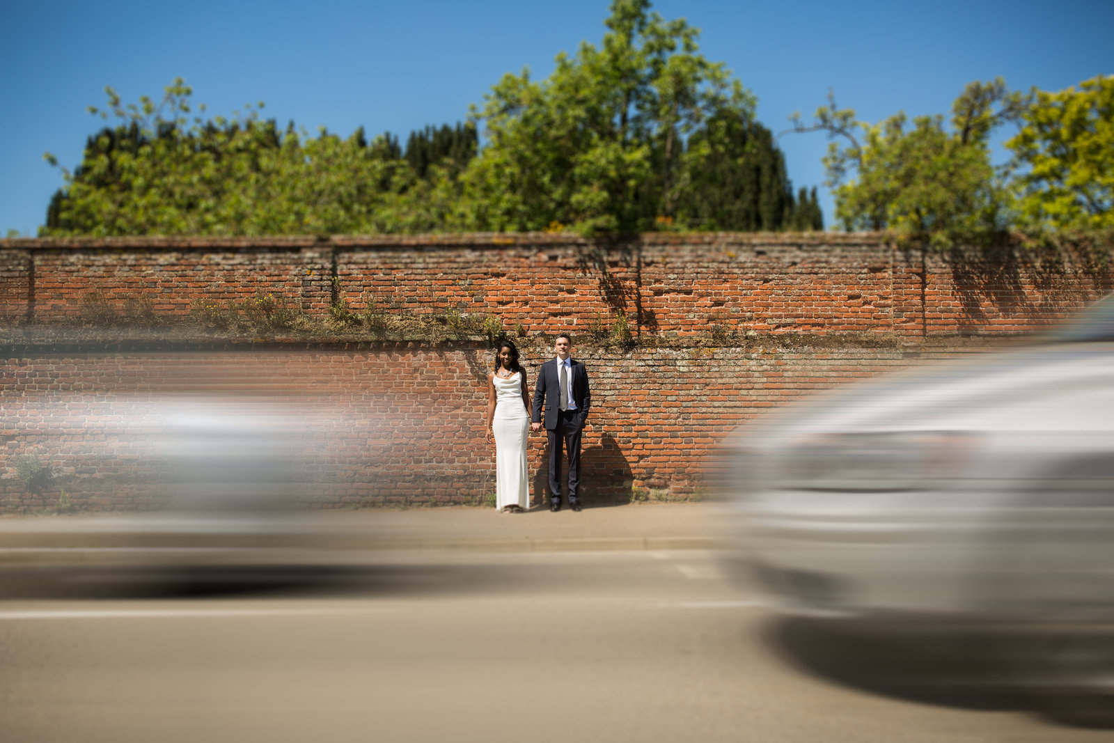 A bride and groom stand against a wall in Norwich. There are motion blurred cars moving in front of them whilst they hold hands and smile at the camera.