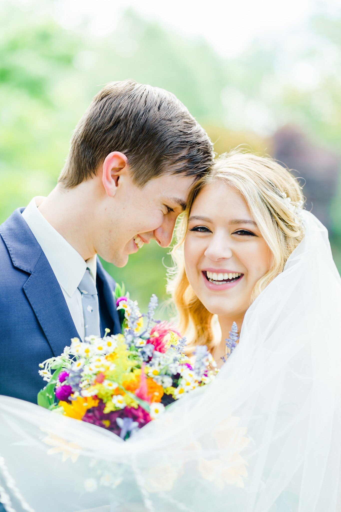 Bride and groom laughing with colorful bouquet