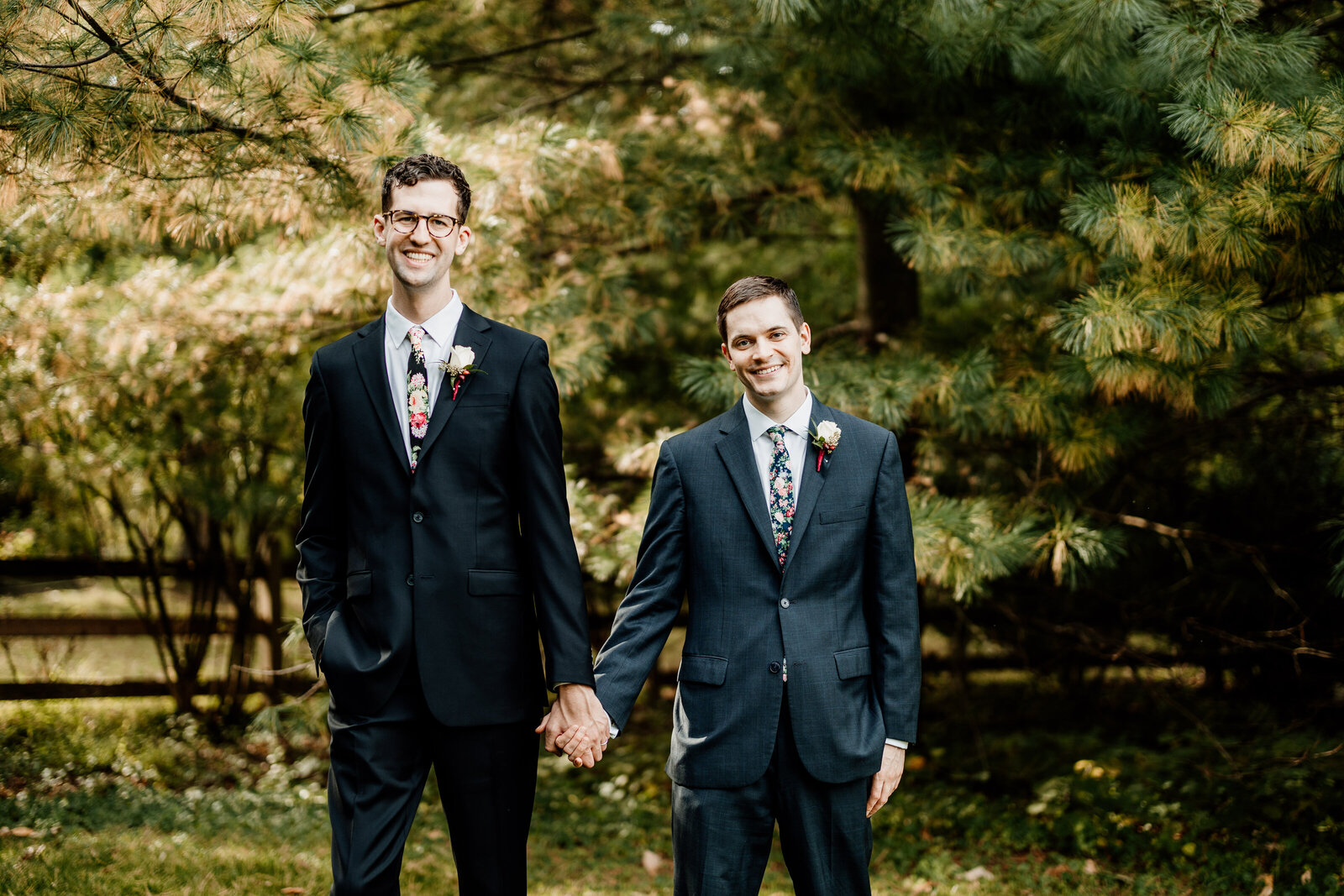 gay grooms holding hands in nature garden