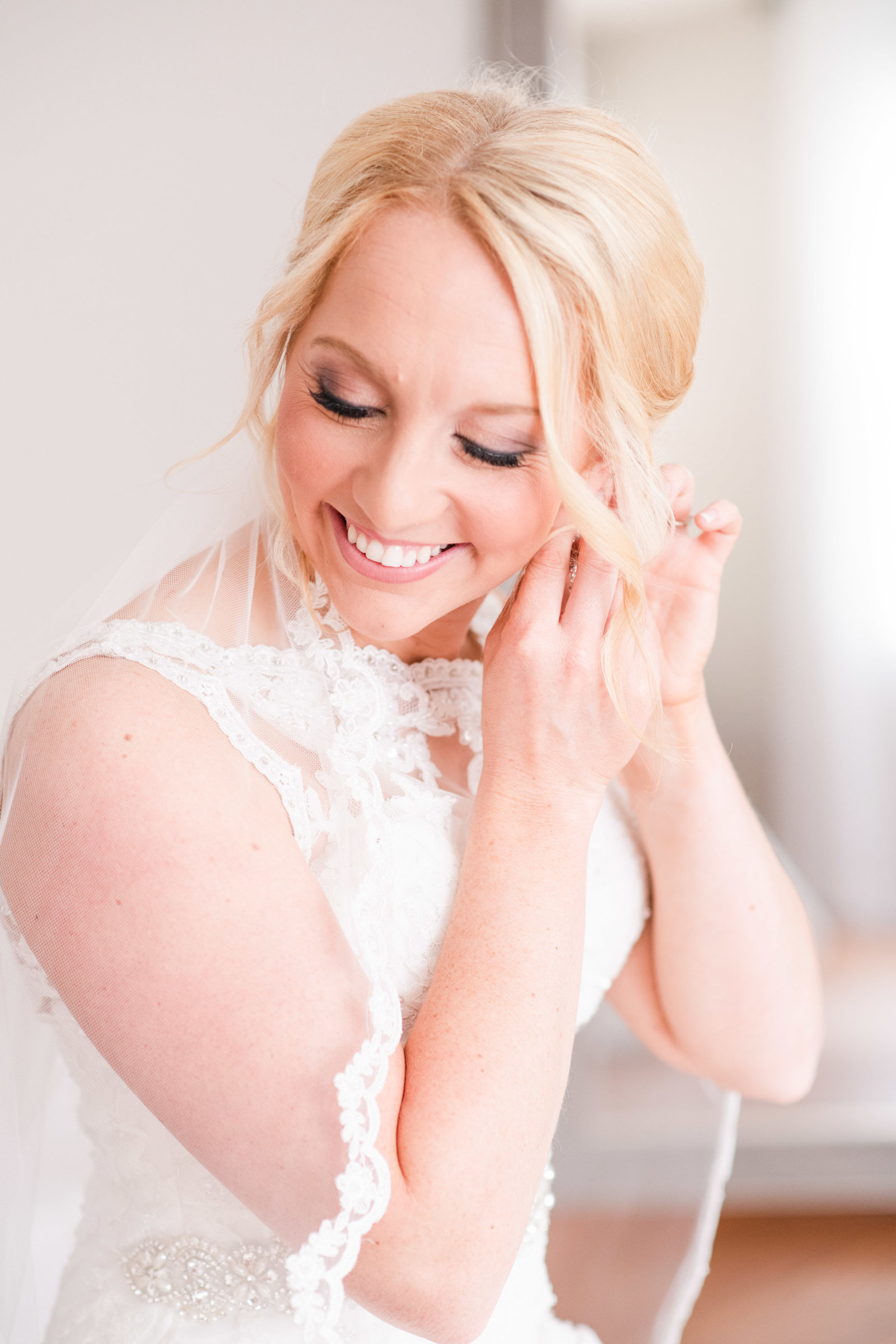 bride putting on earrings while getting ready for wedding