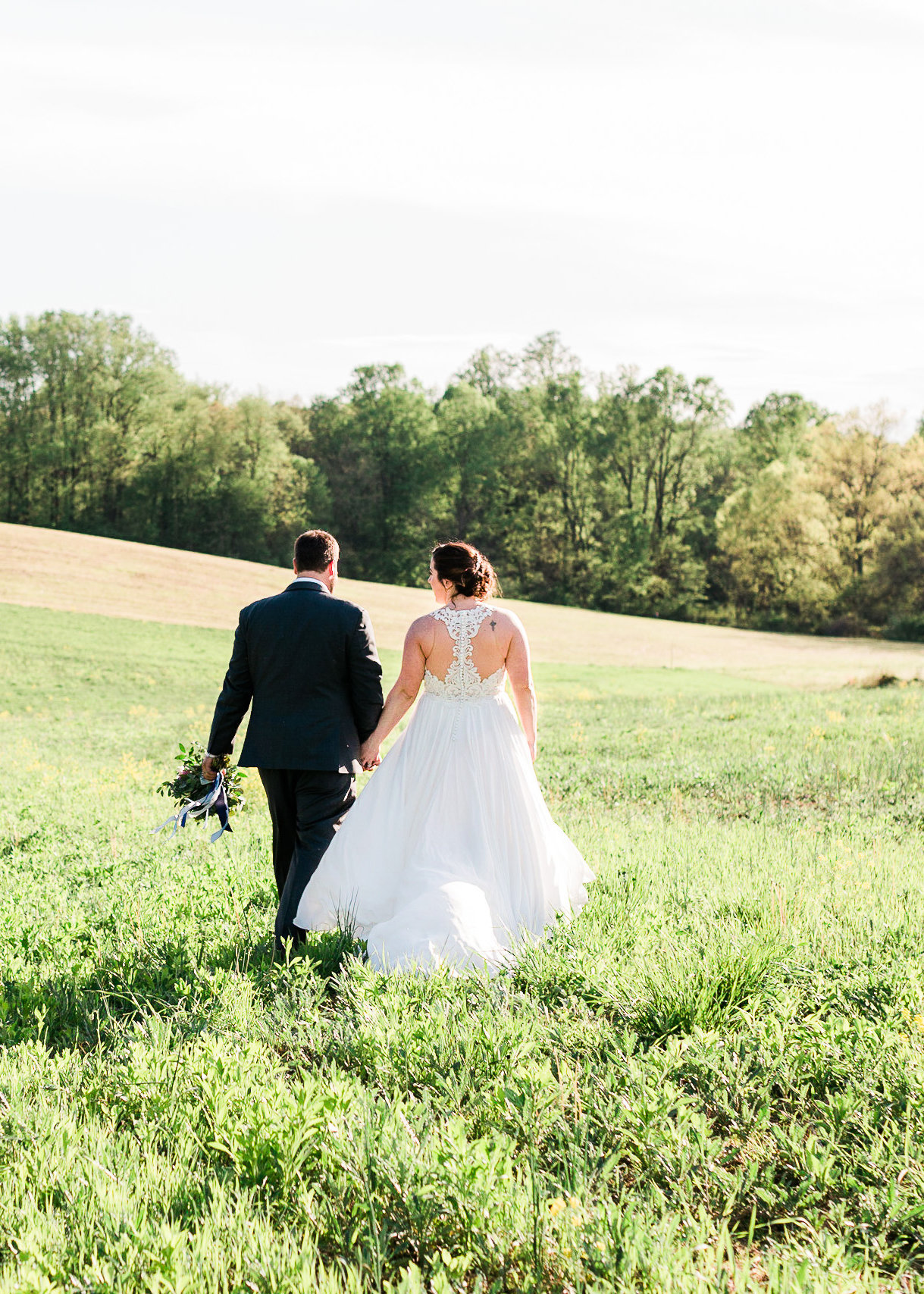Bride with flowing dress and groom in a gray suit walking away in a bright field. Maryland Wedding.