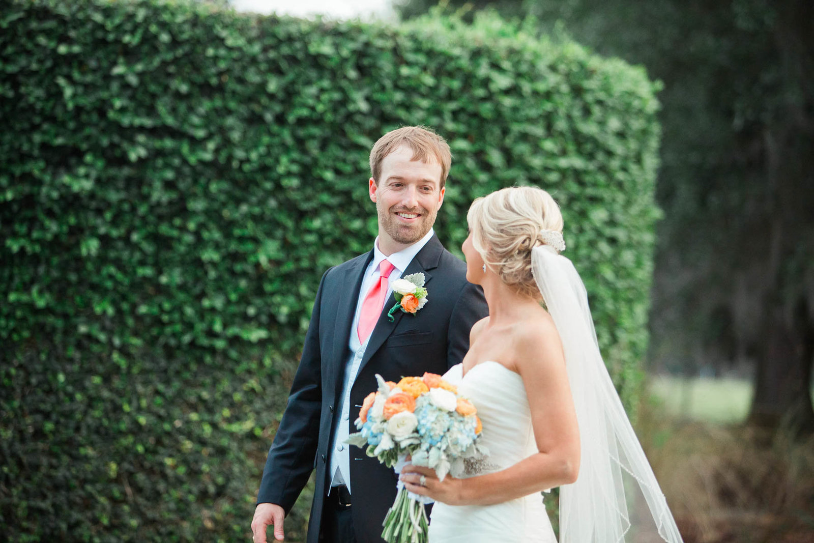 Bride and groom smile by ivy covered wall, Dunes West Golf and River Club, Mt Pleasant, South Carolina