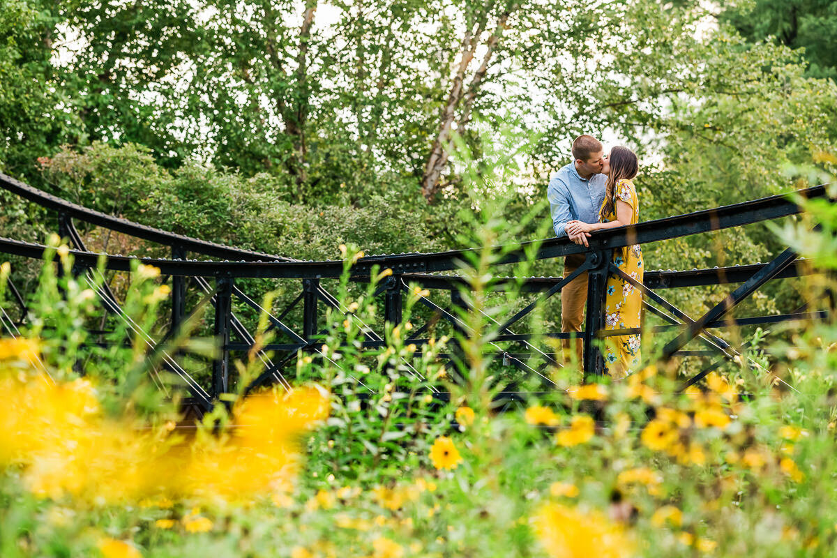 Engaged couple kissing on the Victorian Footbridge surrounded by flowers in Forest Park in St. Louis