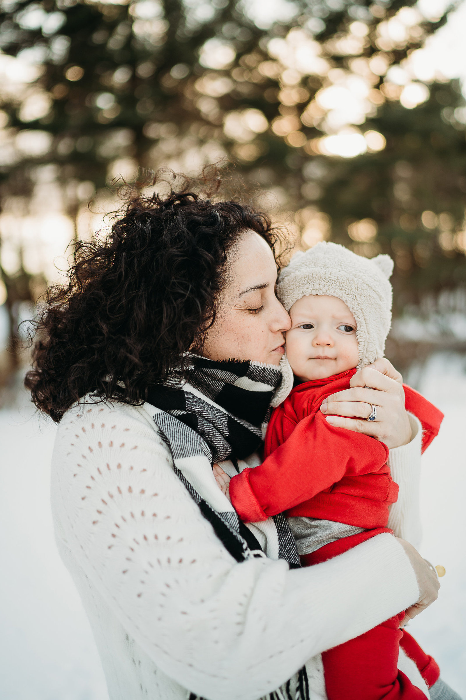 mother kisses her baby boy in a red snow suit for winter family photos in framingham