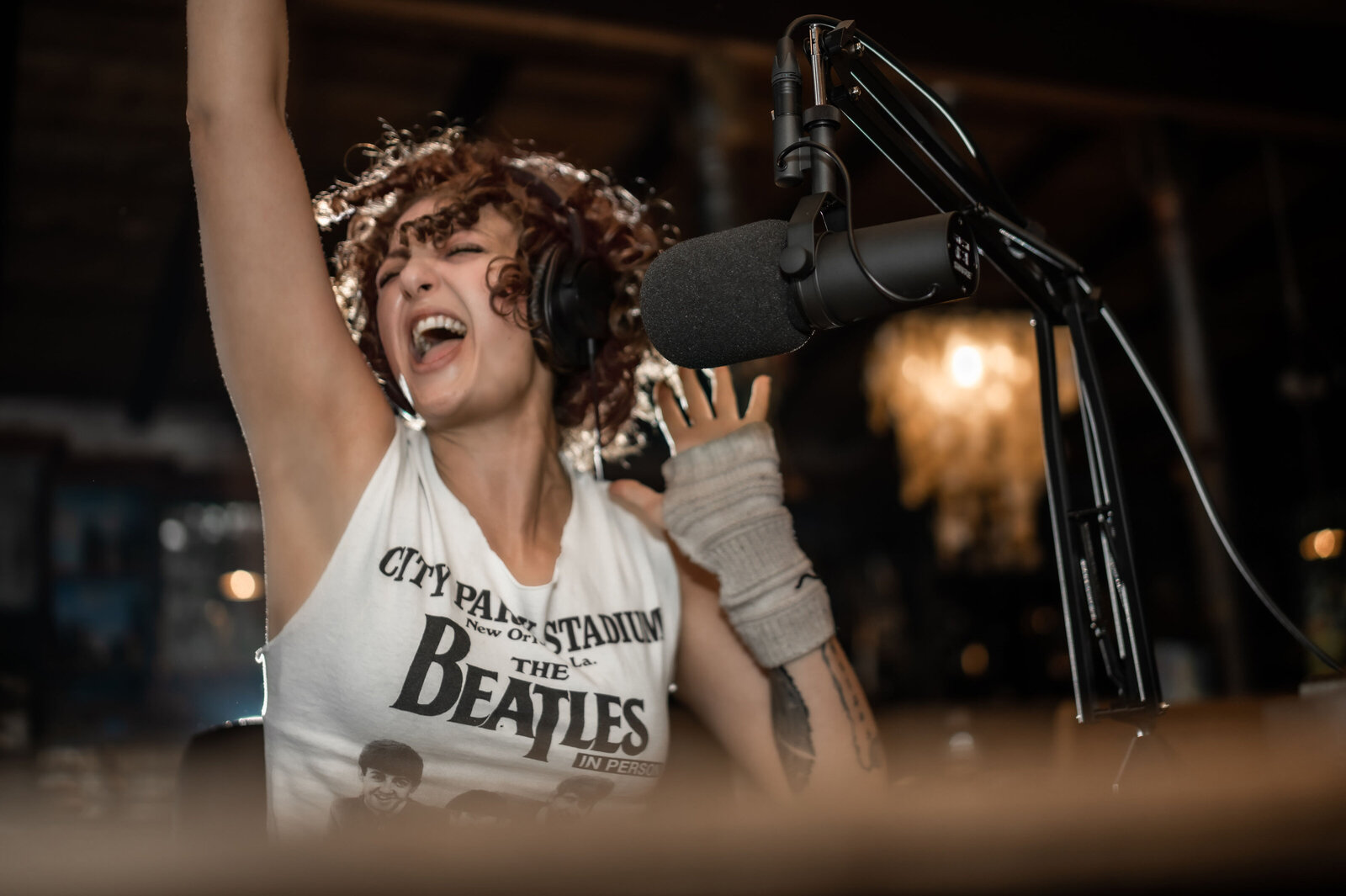 Photo of Hannah Ellaham the BYOBrand Podcast Host - Hands Thrown Up  Screaming into the microphone