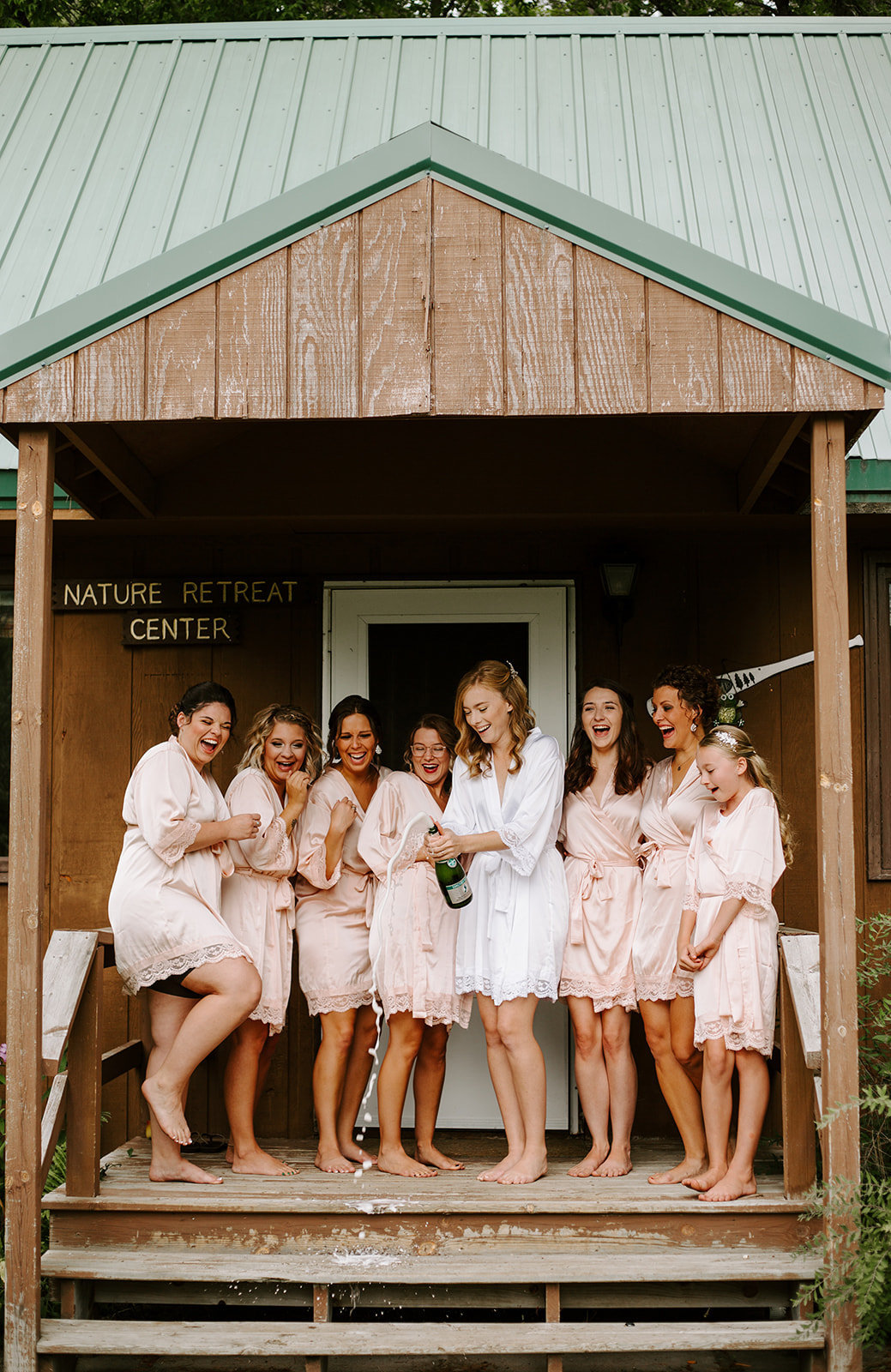 Bride and her bridesmaids popping champagne on the steps of a cabin in their robes on her Minneapolis Wedding day