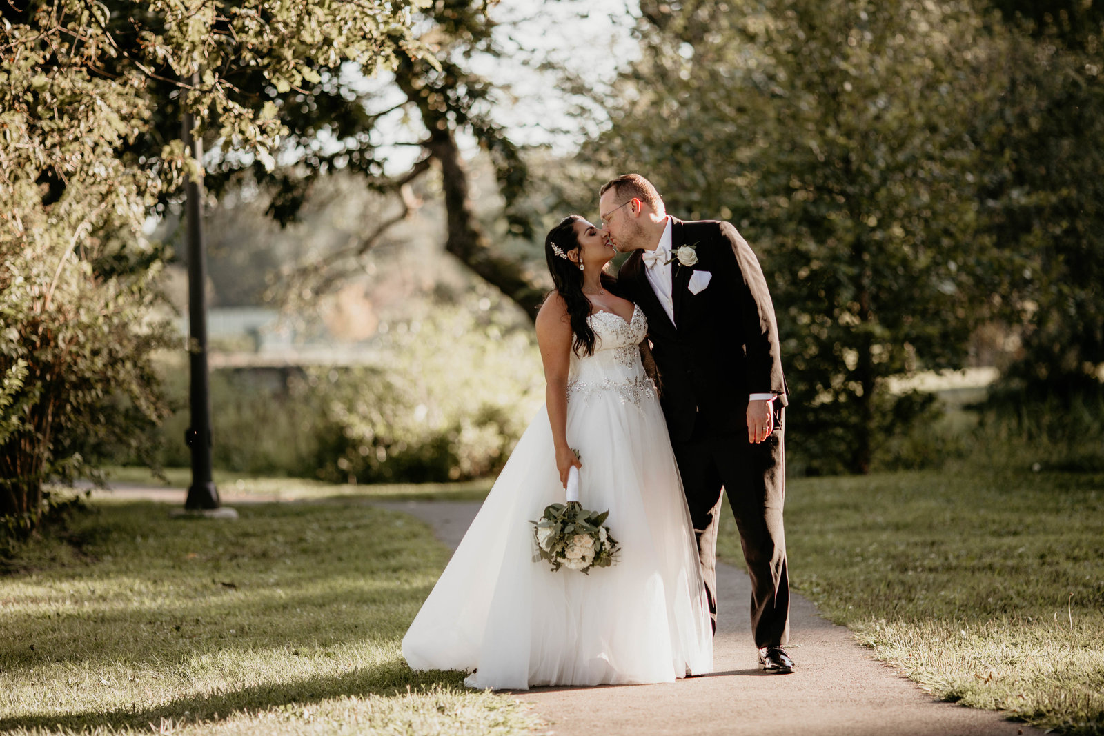 bride and groom kiss in a park.