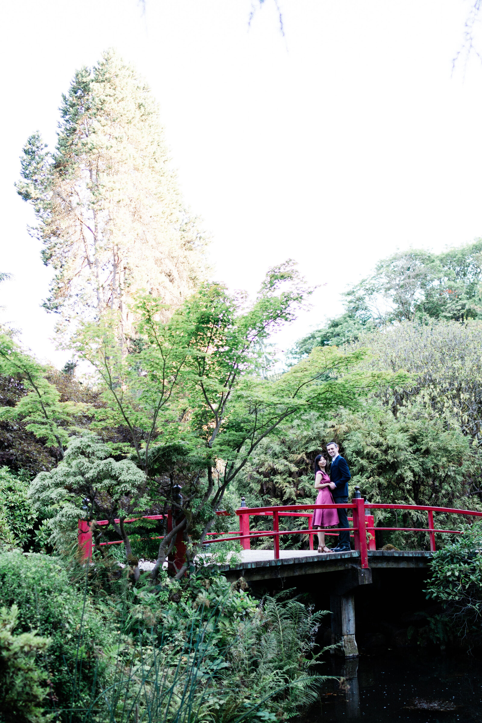 Couple kisses on famous red bridge at Kubota Garden, on list of best locations for engagement photos in Seattle