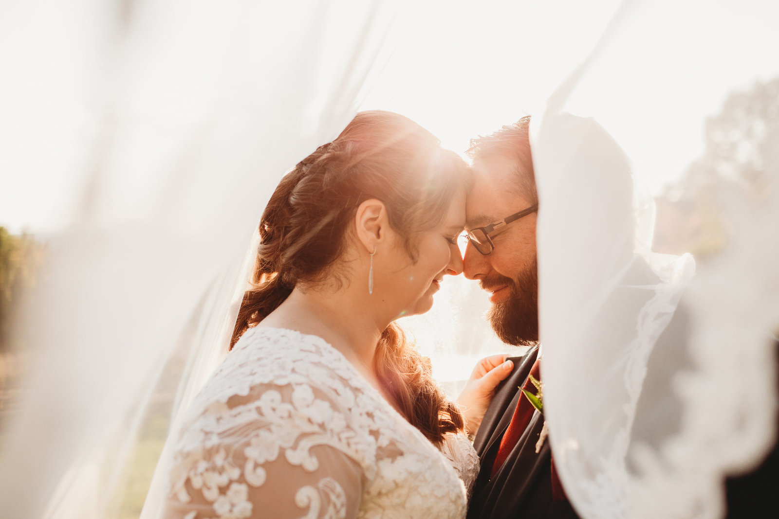 bride and groom stand nose to nose under veil