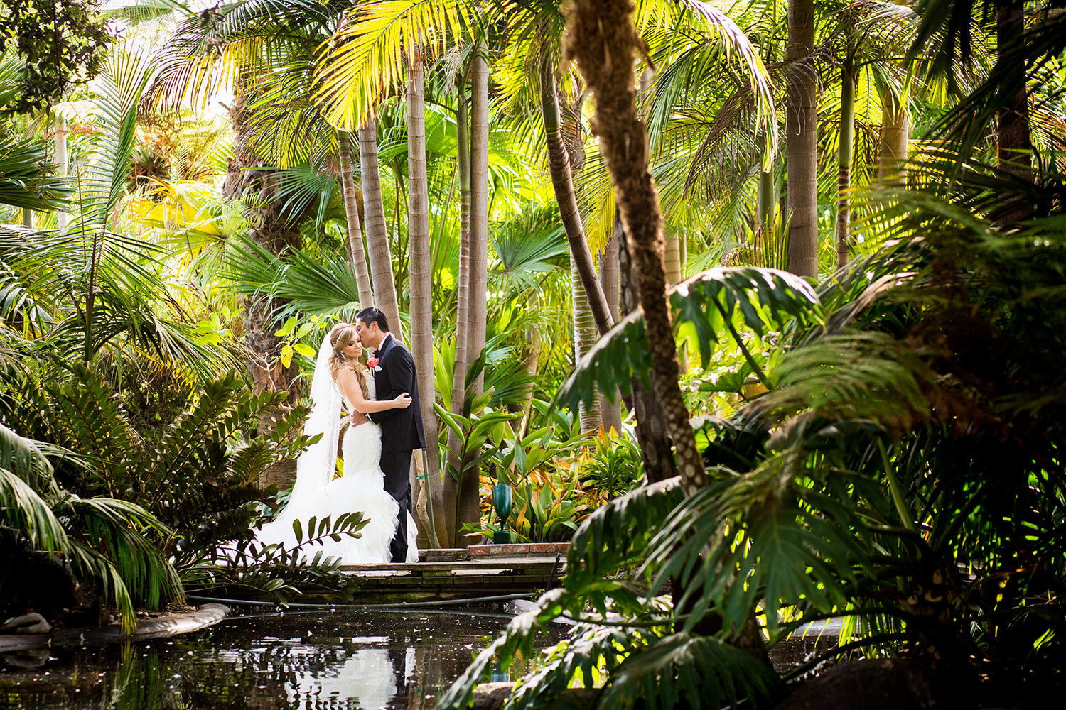 bride and groom on bridge with tropical flowers