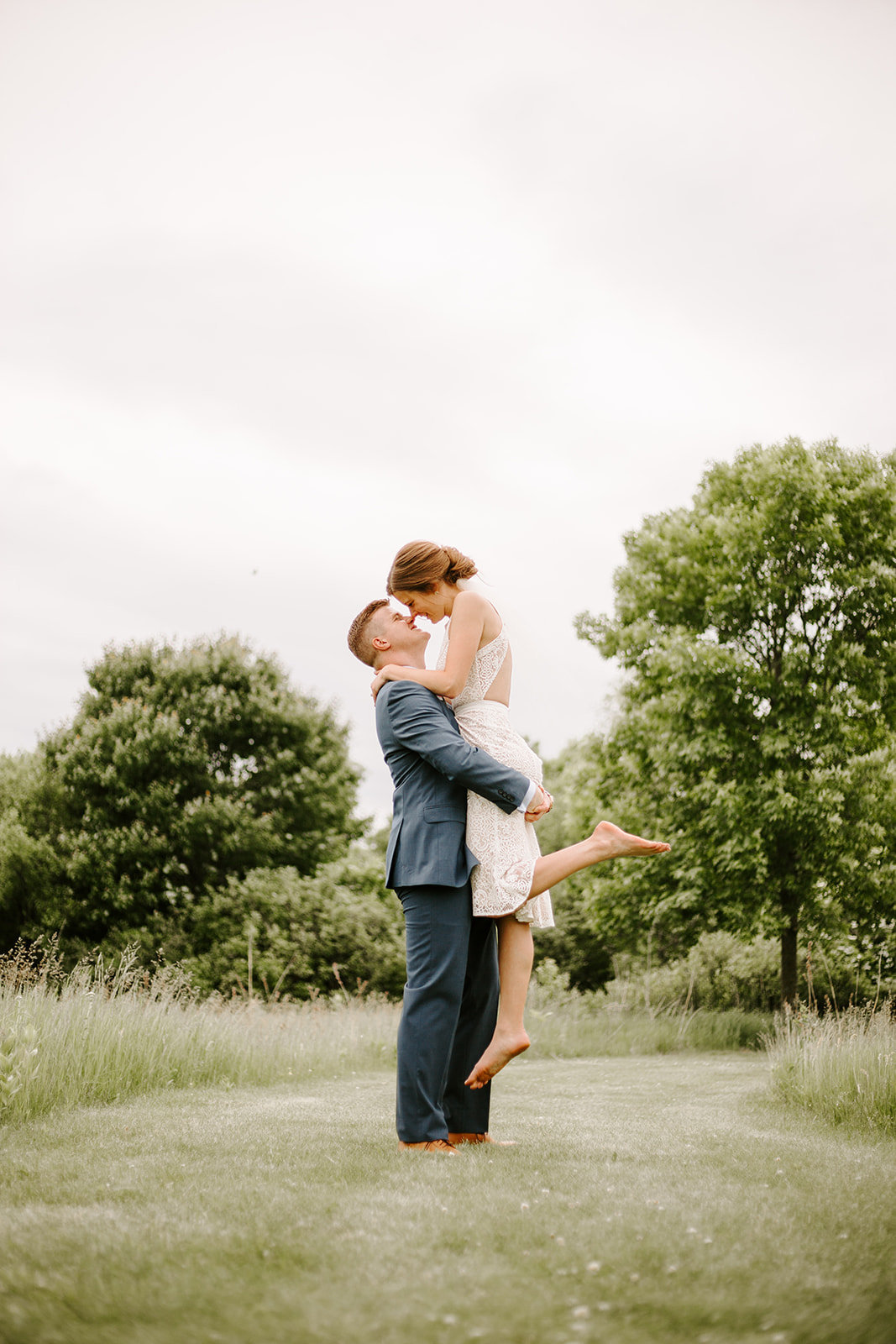 Groom lifting up his bride in a field during their Minneapolis Elopement