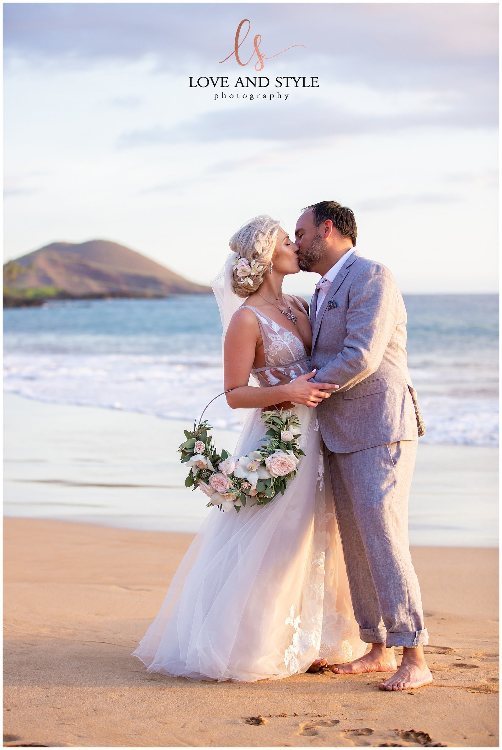 Bride and groom kissing on the beach with ocean and sunset background