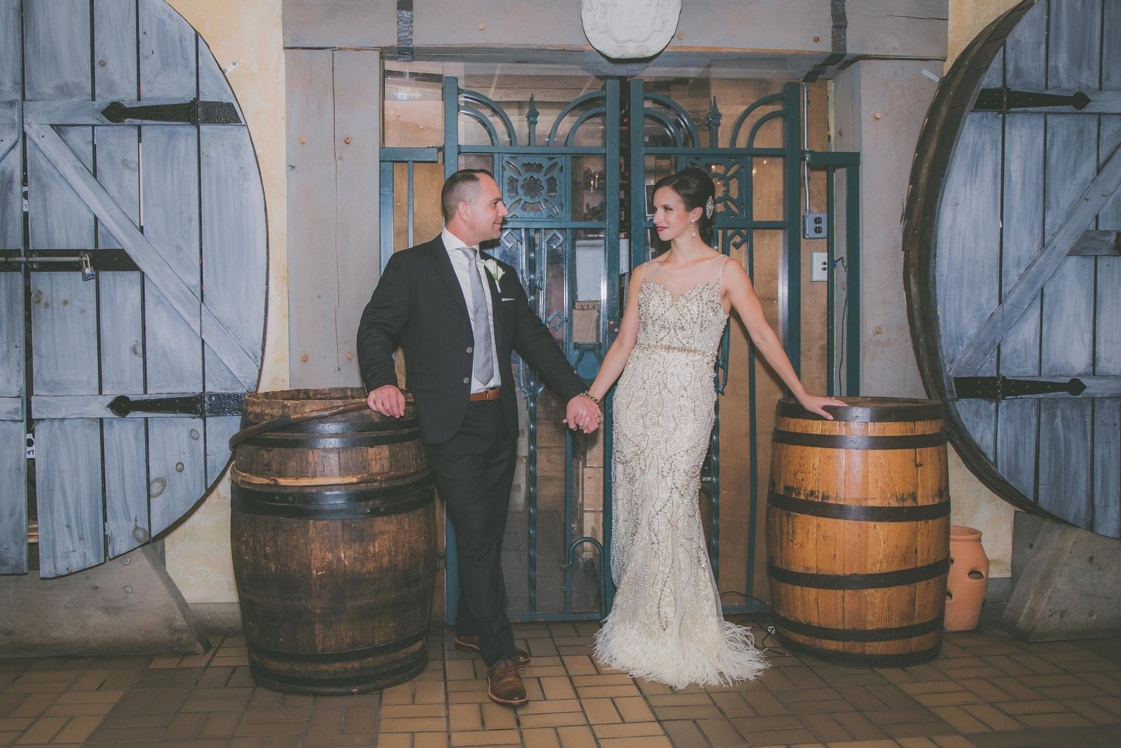 Bride and groom look and smile at each other in winery basement.