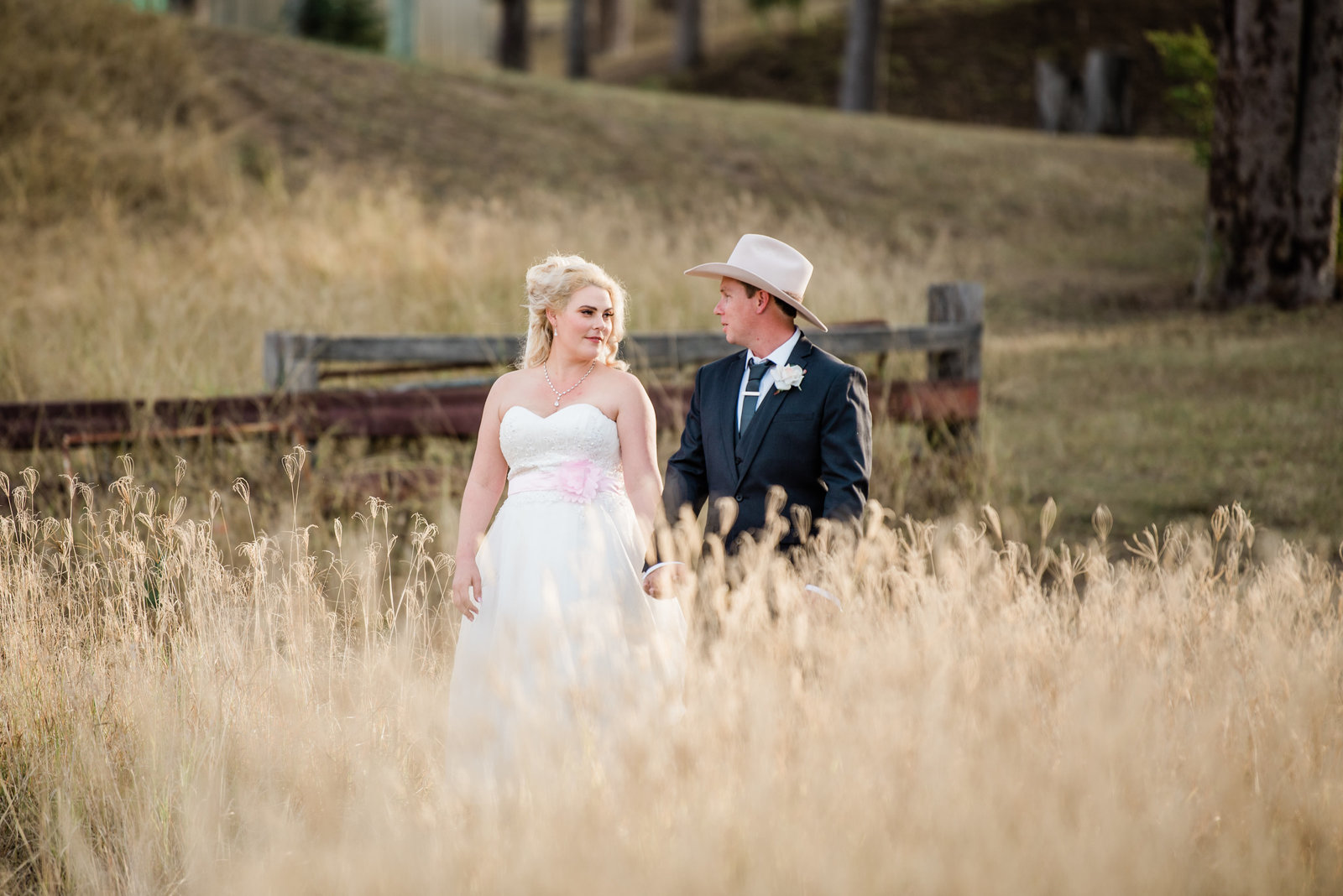 Minden-Retreat-Country-wedding-bride-and-groom-walk-in-grassy-field (1 of 1)